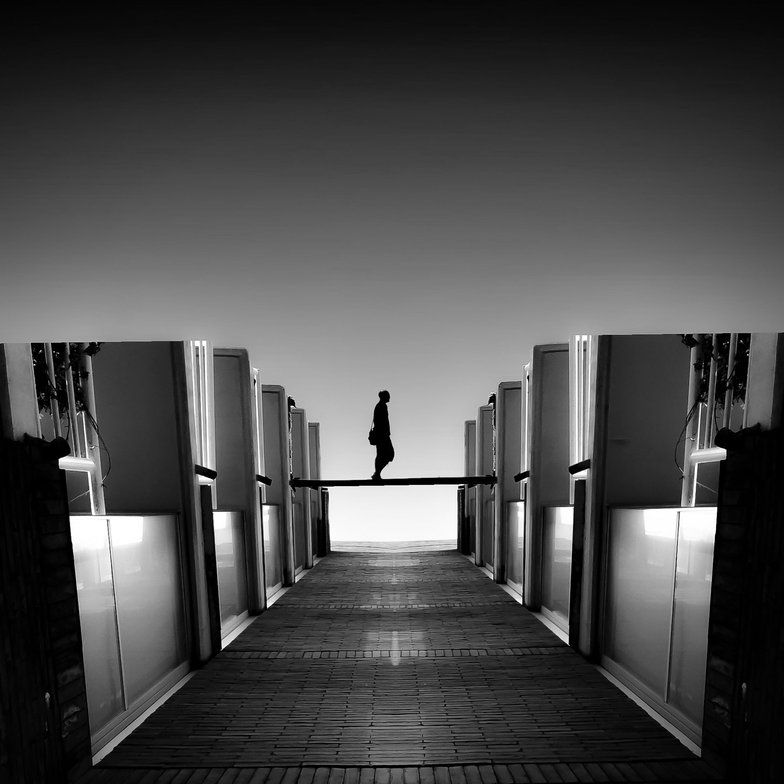 full length, built structure, architecture, walking, clear sky, building exterior, rear view, the way forward, lifestyles, men, copy space, leisure activity, diminishing perspective, railing, city, person, silhouette, city life