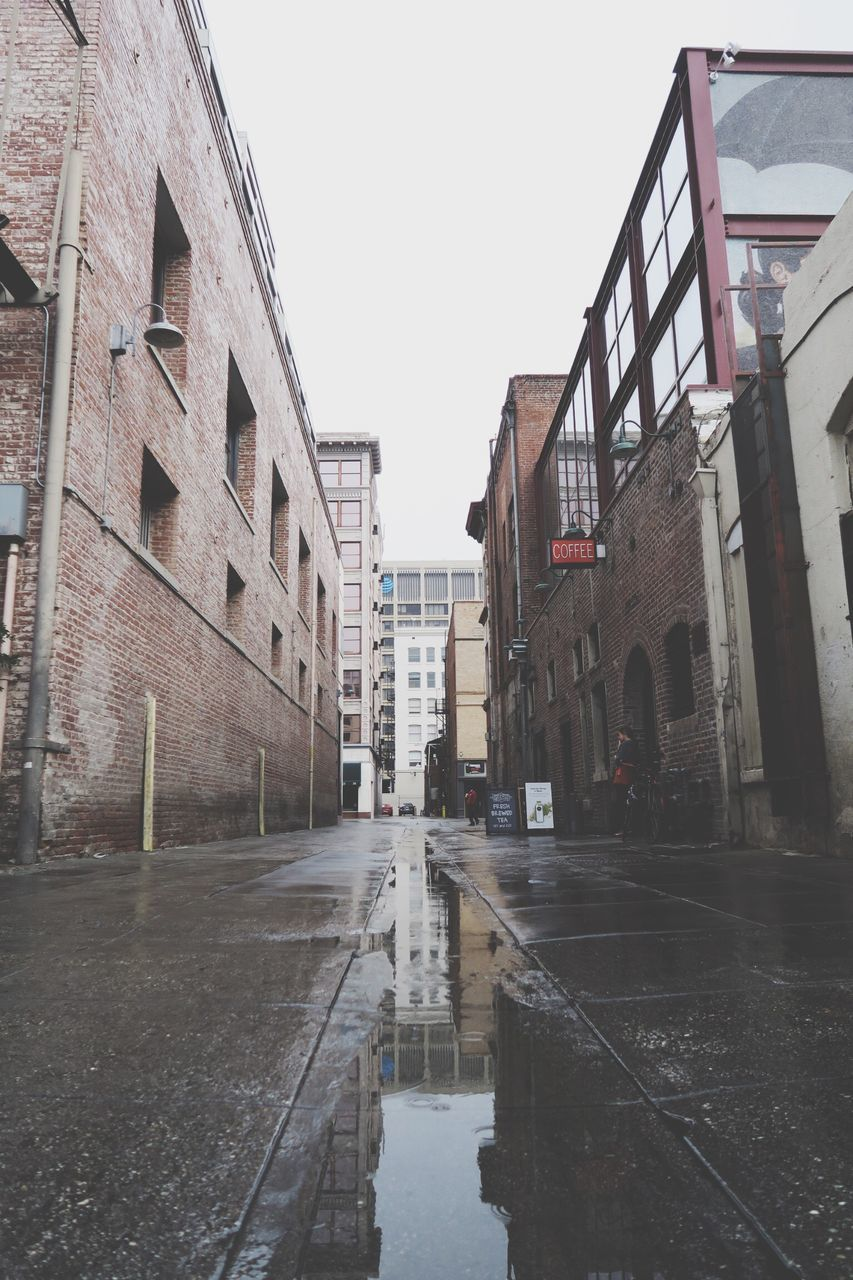 architecture, building exterior, built structure, wet, water, puddle, street, outdoors, clear sky, sky, no people, city, day