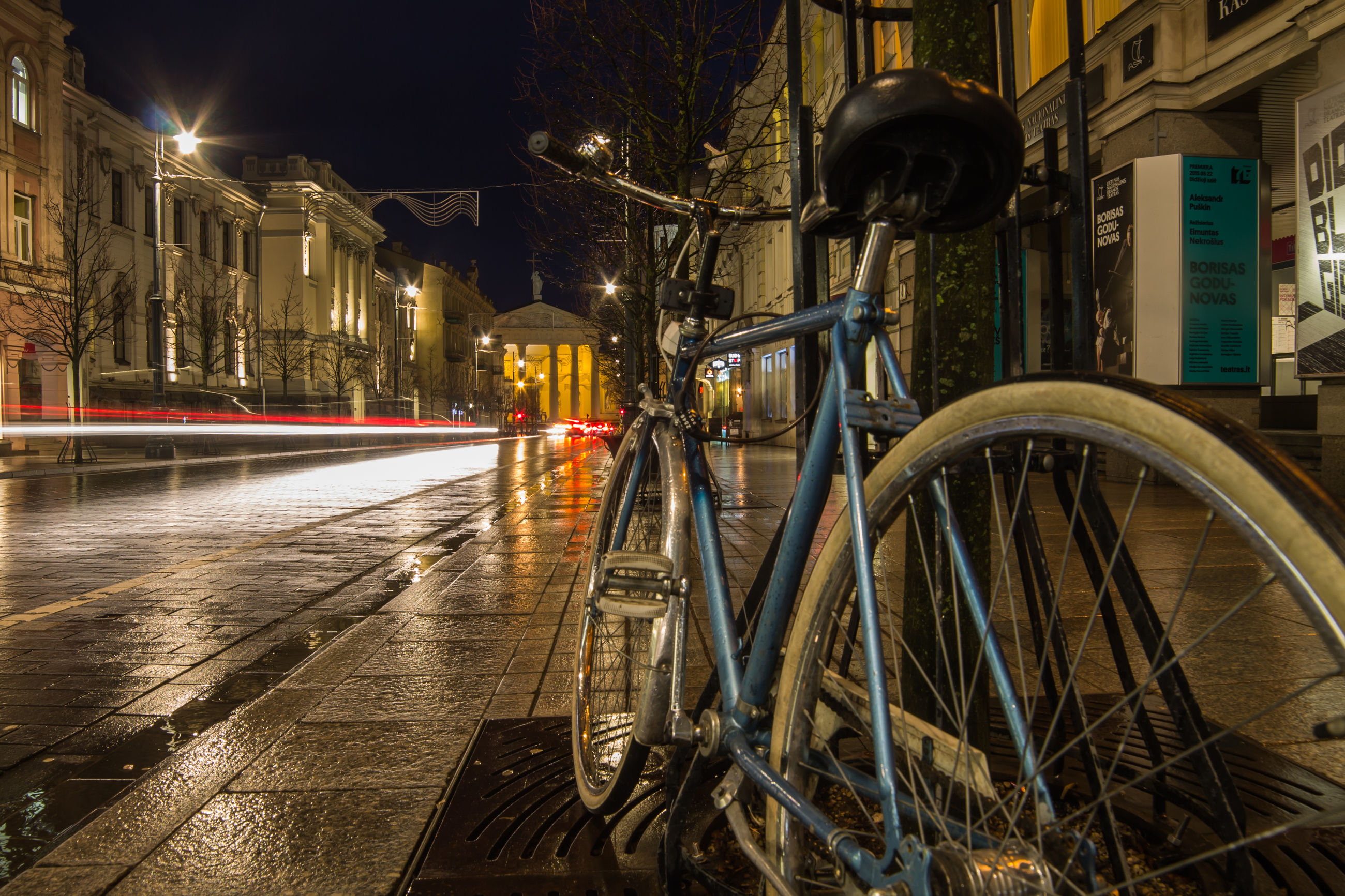 building exterior, architecture, built structure, night, city, illuminated, transportation, street, mode of transport, bicycle, land vehicle, building, city life, motion, water, street light, incidental people, residential building