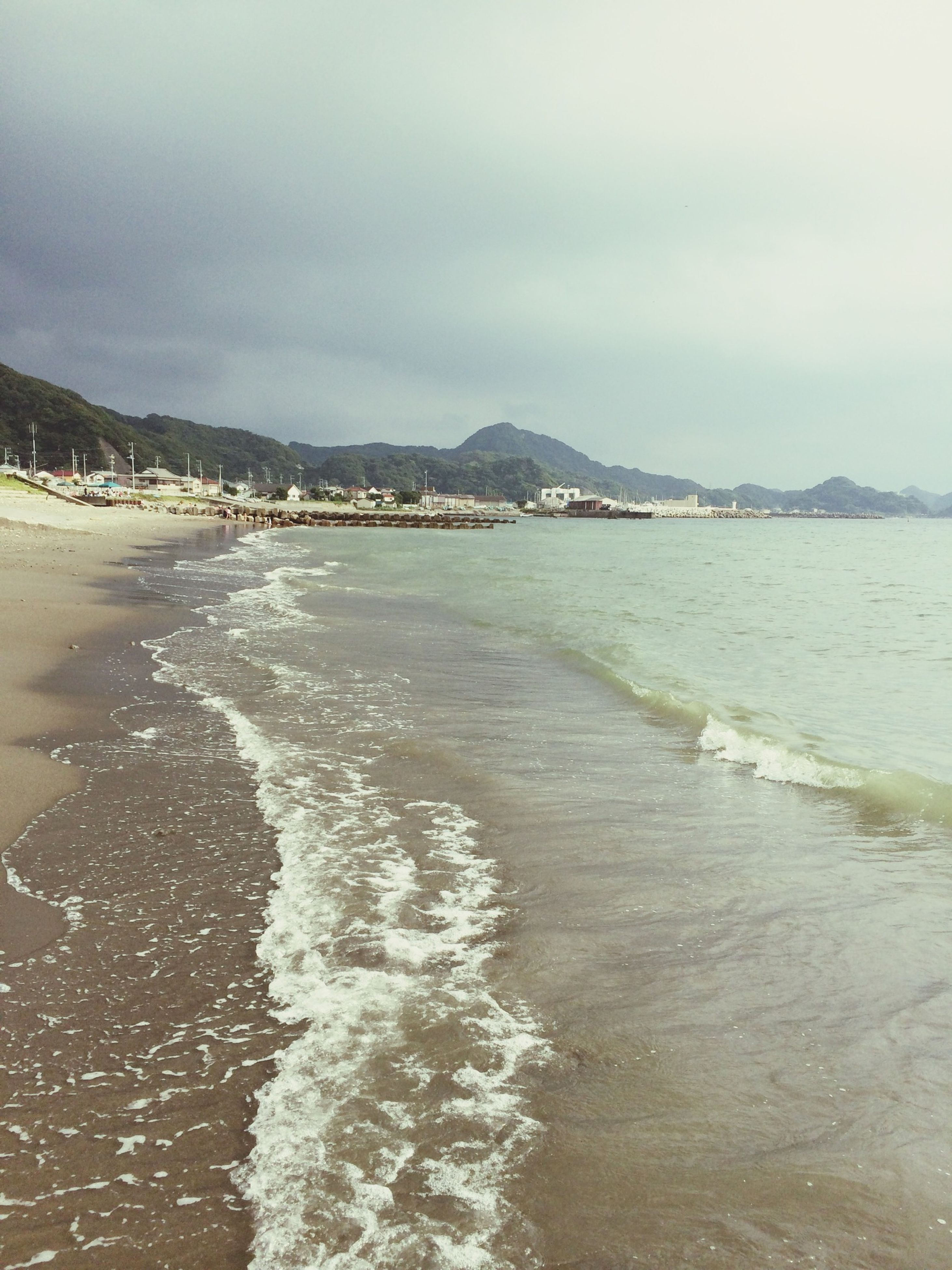 water, sea, beach, sky, tranquil scene, scenics, shore, tranquility, beauty in nature, sand, nature, wave, cloud - sky, mountain, coastline, surf, cloudy, idyllic, waterfront, cloud