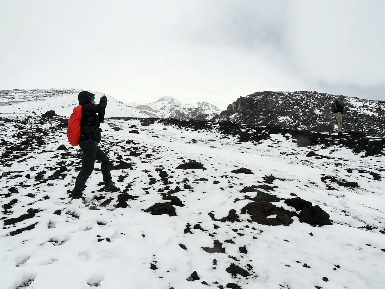 Side View Of Person With Red Backpack Walking On Snowy Mountain At Cotopaxi National Park