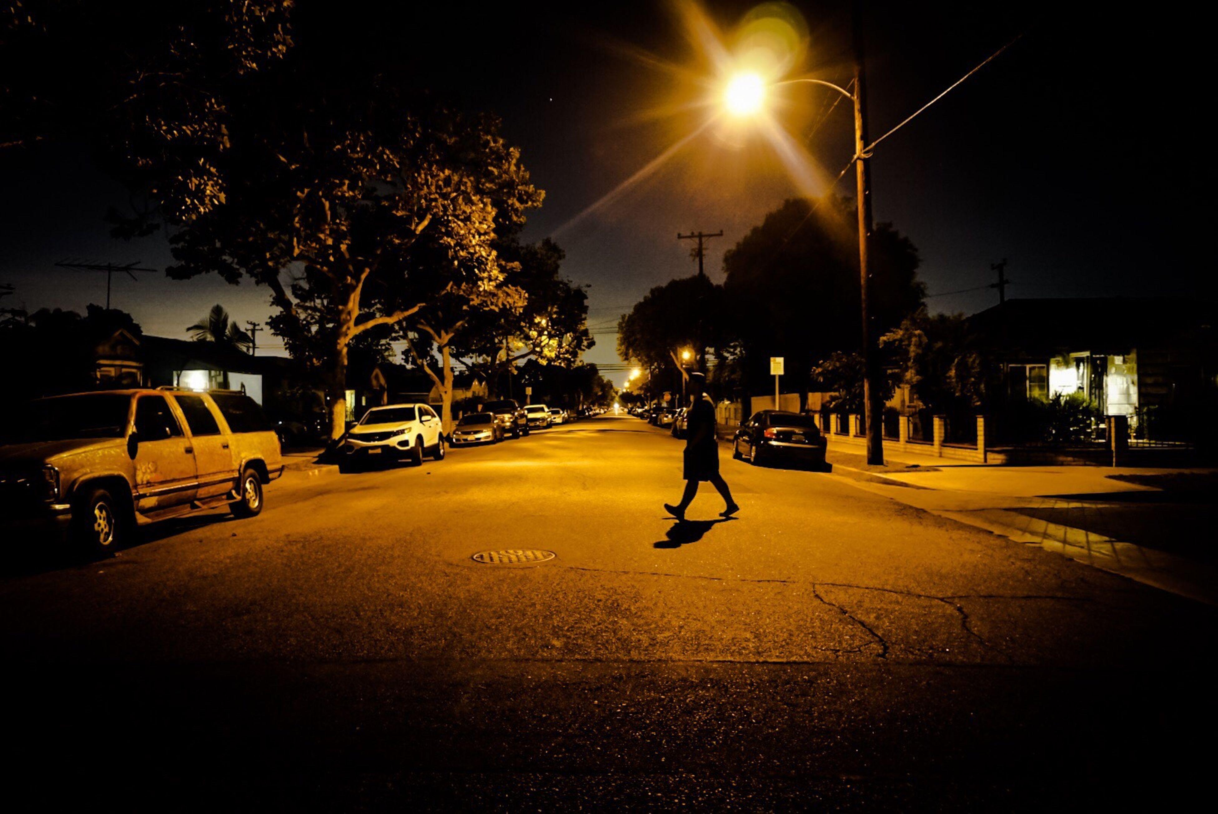 street, tree, full length, road, car, transportation, night, walking, illuminated, land vehicle, lens flare, sunbeam, outdoors, sky, light beam, city life