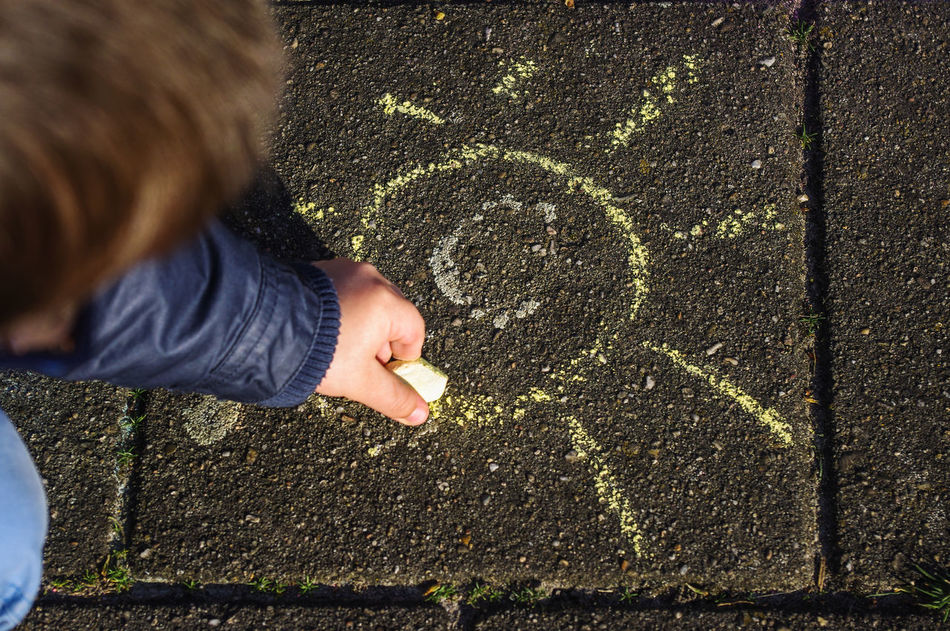 Kid drawing a sun with chalk Adult Chalk Drawing Child Childhood Children Only Creativity Day Drawing - Activity Floor Hand Human Body Part Leisure Activity Lifestyles One Person Outdoors Pavement People Playing Real People Street Sun