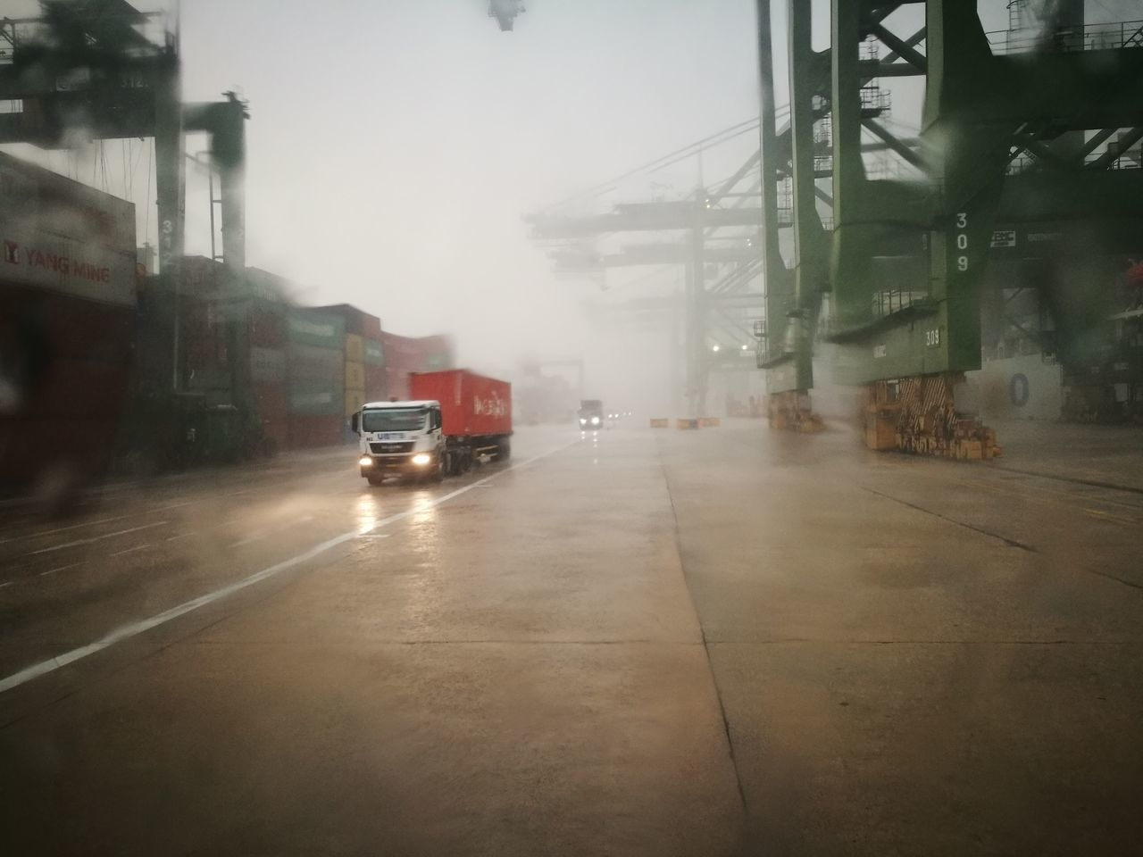 transportation, land vehicle, fog, car, weather, mode of transport, architecture, the way forward, wet, road, built structure, day, outdoors, no people, building exterior, city, sky