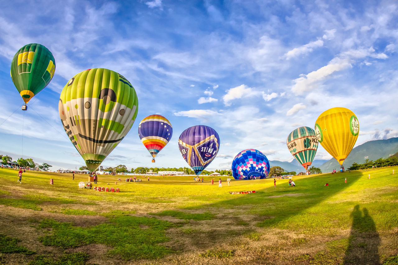 Air Vehicle Ballooning Festival Blue Cloud - Sky Day Flying Grass Green Color Hot Air Balloon Multi Colored No People Outdoors Sky