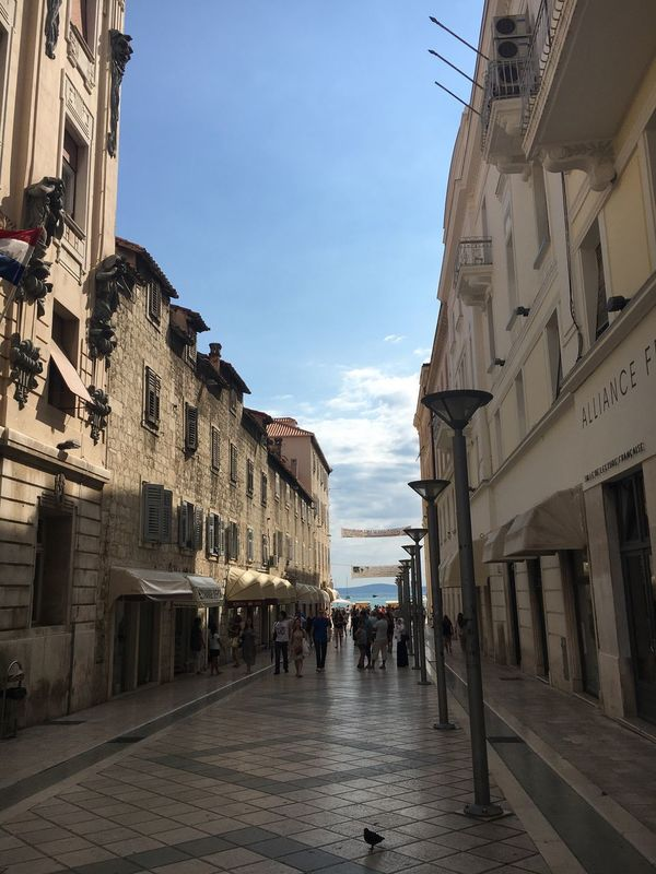 View of street in Split Architecture Built Structure Building Exterior Sky Person Large Group Of People City The Way Forward City Life Day Outdoors Footpath Cloud - Sky Old Town Street View Of Sea Afternoon Bird Street Lamps No Faces