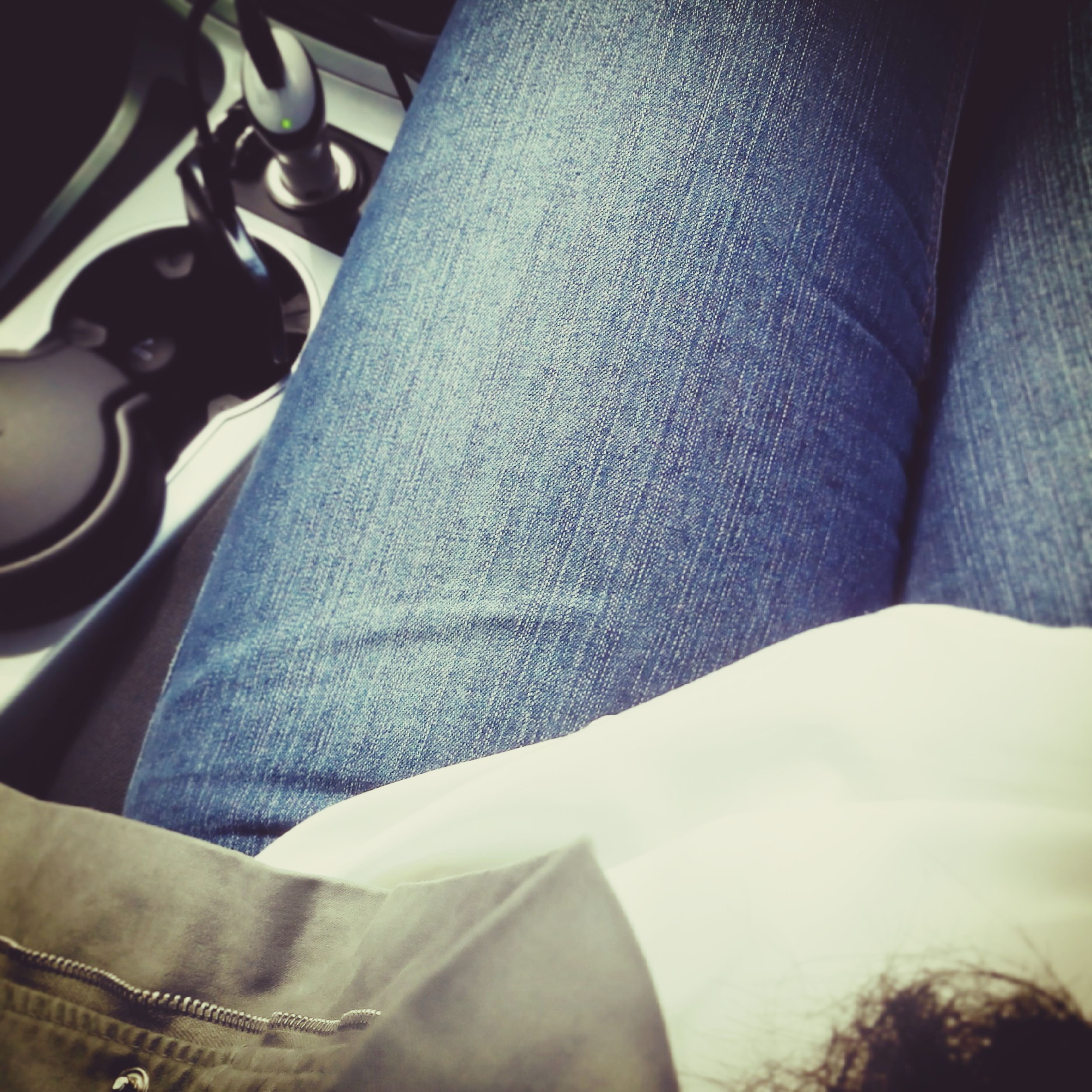 person, low section, indoors, close-up, part of, jeans, midsection, textile, personal perspective, human foot, high angle view, day, vehicle interior, relaxation, lifestyles, sunlight, unrecognizable person