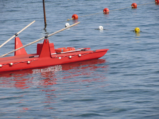 Rowed rescue catamaran at sea waiting for emergency. Tuscany, Italy Catamaran Dinghy Emergency Equipment Escape Harbor Harbour Lie Lifeboat Lifesaver Marina Mediterranean  Navigation Nobody Oar Pier Preserver Rescue Rowed Safety Save Sea Summer Survival Vessel