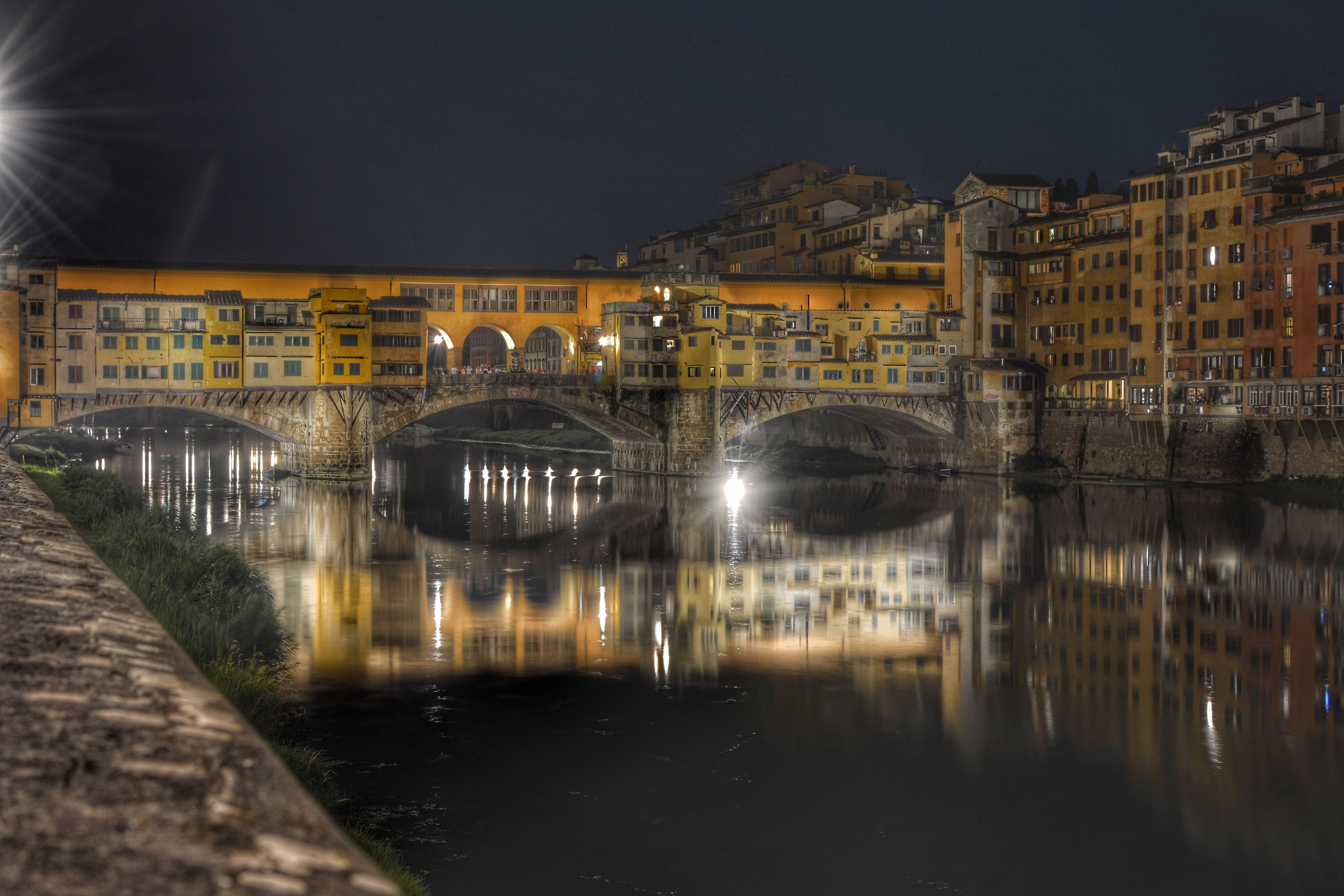 architecture, built structure, building exterior, illuminated, connection, bridge - man made structure, water, reflection, night, city, waterfront, river, arch, residential building, residential structure, engineering, standing water, city life, outdoors, ponte vecchio, sky, residential district, bridge, electric light, canal, no people
