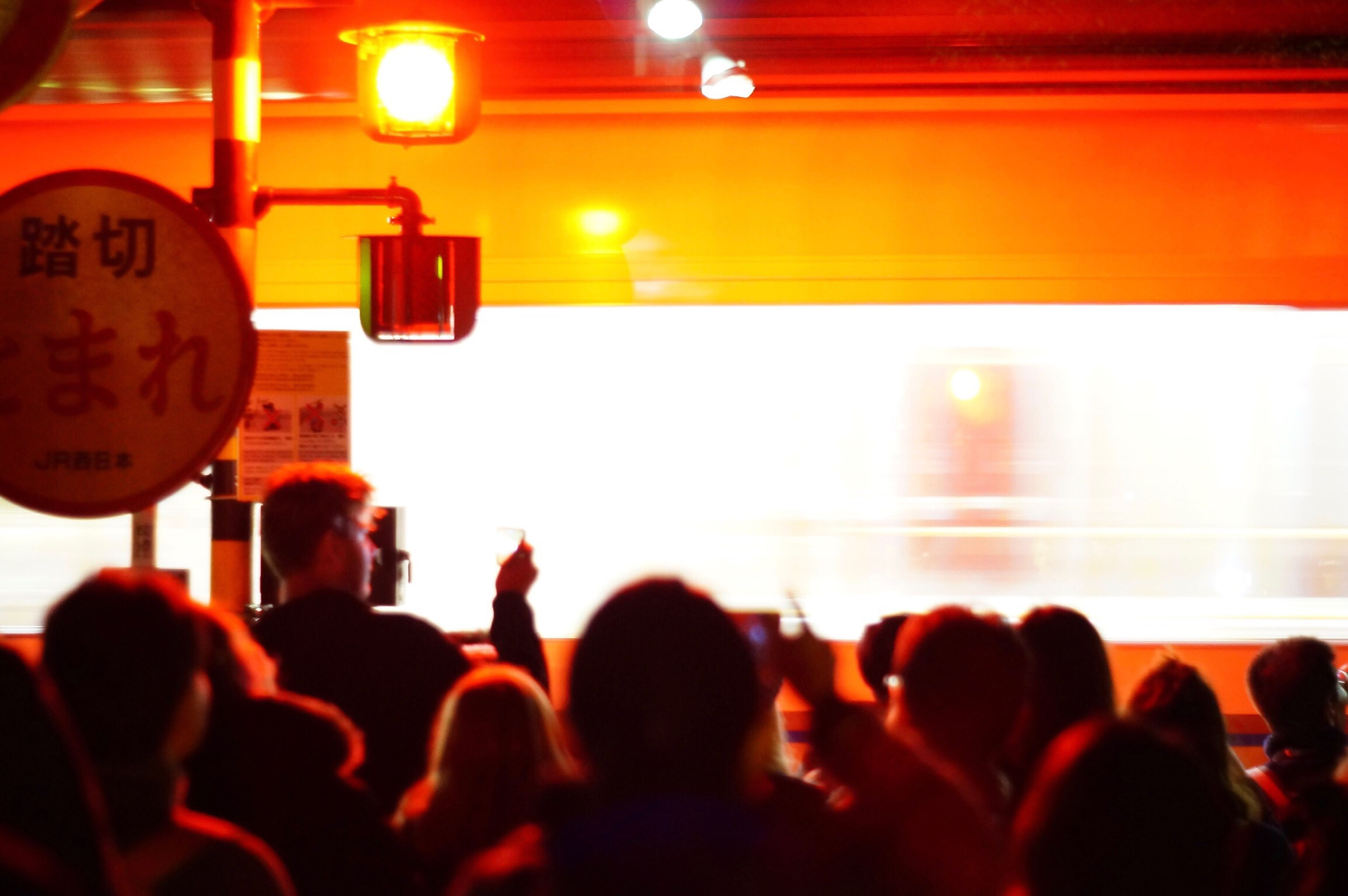 indoors, illuminated, large group of people, lighting equipment, men, light - natural phenomenon, group of people, crowd, person, performance, nightlife, spotlight, social gathering, back lit, journey