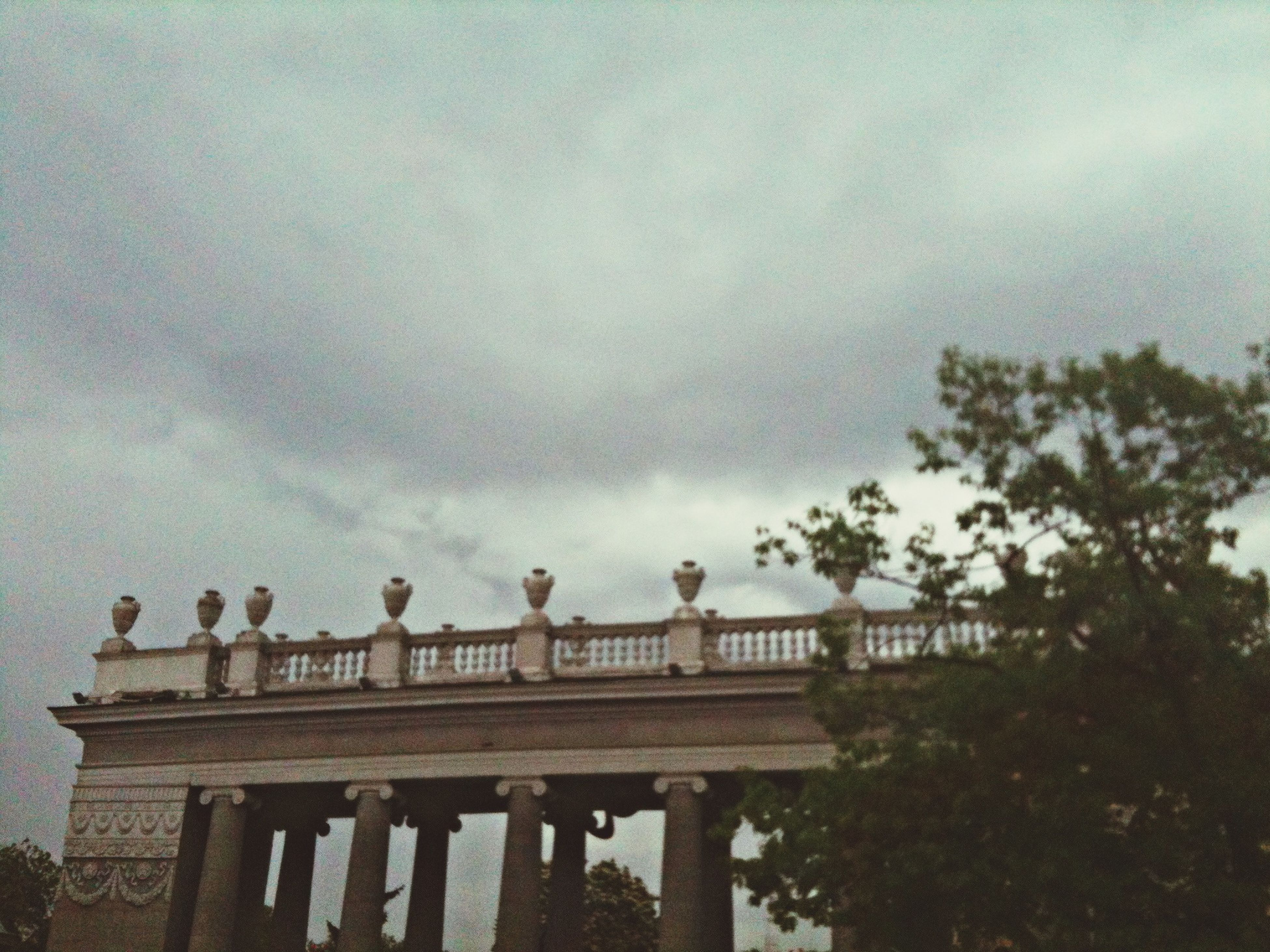 architecture, sky, low angle view, built structure, cloud - sky, cloudy, architectural column, building exterior, tree, cloud, overcast, outdoors, column, statue, day, history, art and craft, sculpture, no people, art