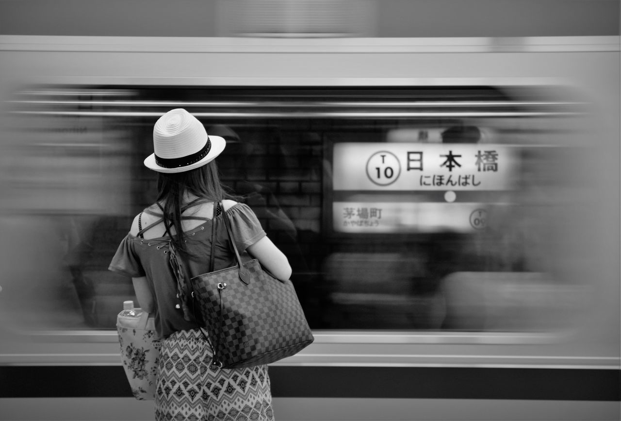Rear View Of Woman Standing By Train Moving At Subway Station