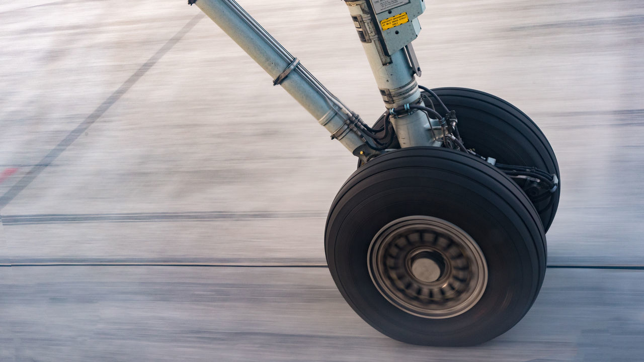 Brakes Close-up Concrete Concrete Pavement Cropped Day Focus On Foreground Grey Grey Pavement Landing Landing Gear Metallic No People Part Of Plane Runaway Speed Tire Wood - Material Wooden