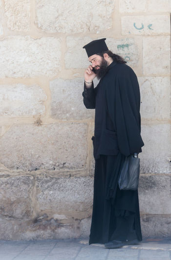 Jerusalem, Israel, July 14, 2017 : The clergyman stands and talks on his mobile phone in the old city of Jerusalem, Israel. Ancient Christianity Church Cross East Jesus Man Spirituality Travel Bible Clergyman Conversation Day Holy Israel Jerusalem Men Mobile Old One Person Phone Pilgrimage Priest Religious  Standing