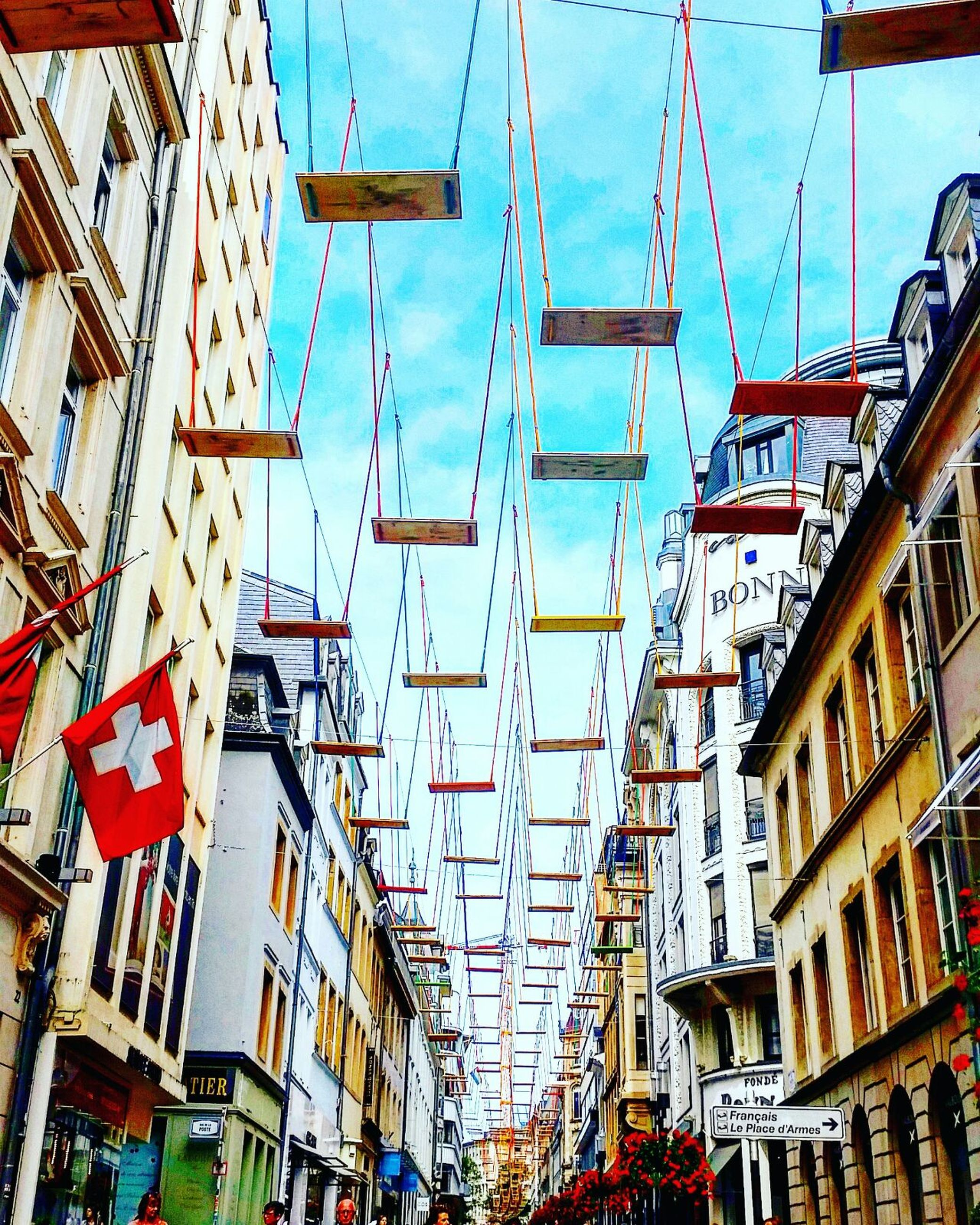 architecture, building exterior, built structure, low angle view, city, building, hanging, sky, in a row, day, development, outdoors, city life, diminishing perspective, no people, large group of objects, modern, power line