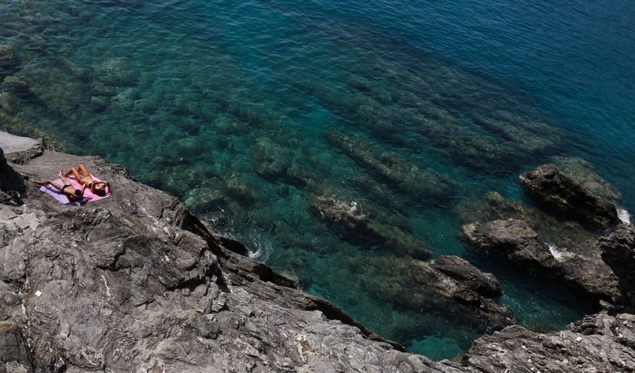 sea, high angle view, rock - object, water, nature, real people, beauty in nature, leisure activity, two people, day, scenics, outdoors, full length, men, vacations, lifestyles, sitting, adult, people