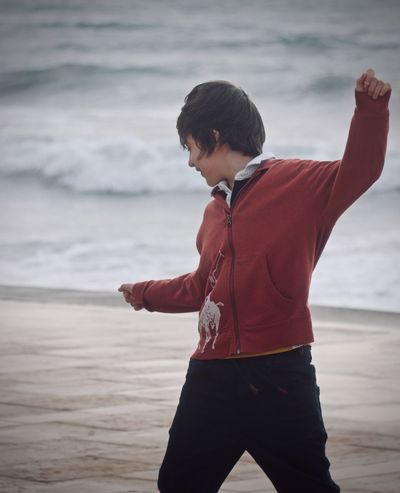 One boy watching the waves in a cloudy and stormy day Cloudy Happiness Stormy Weather Beach Beauty In Nature Childhood Day Horizon Over Water Leisure Time Lifestyles Nature One Boy Only One Person Outdoors People Real People Red Jacket Sand And Sea Sea Sky Standing Sunset Water Wave Young Adult