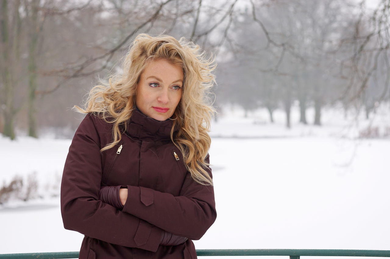 Thoughtful Woman With Arms Crossed Standing On Snow Covered Field