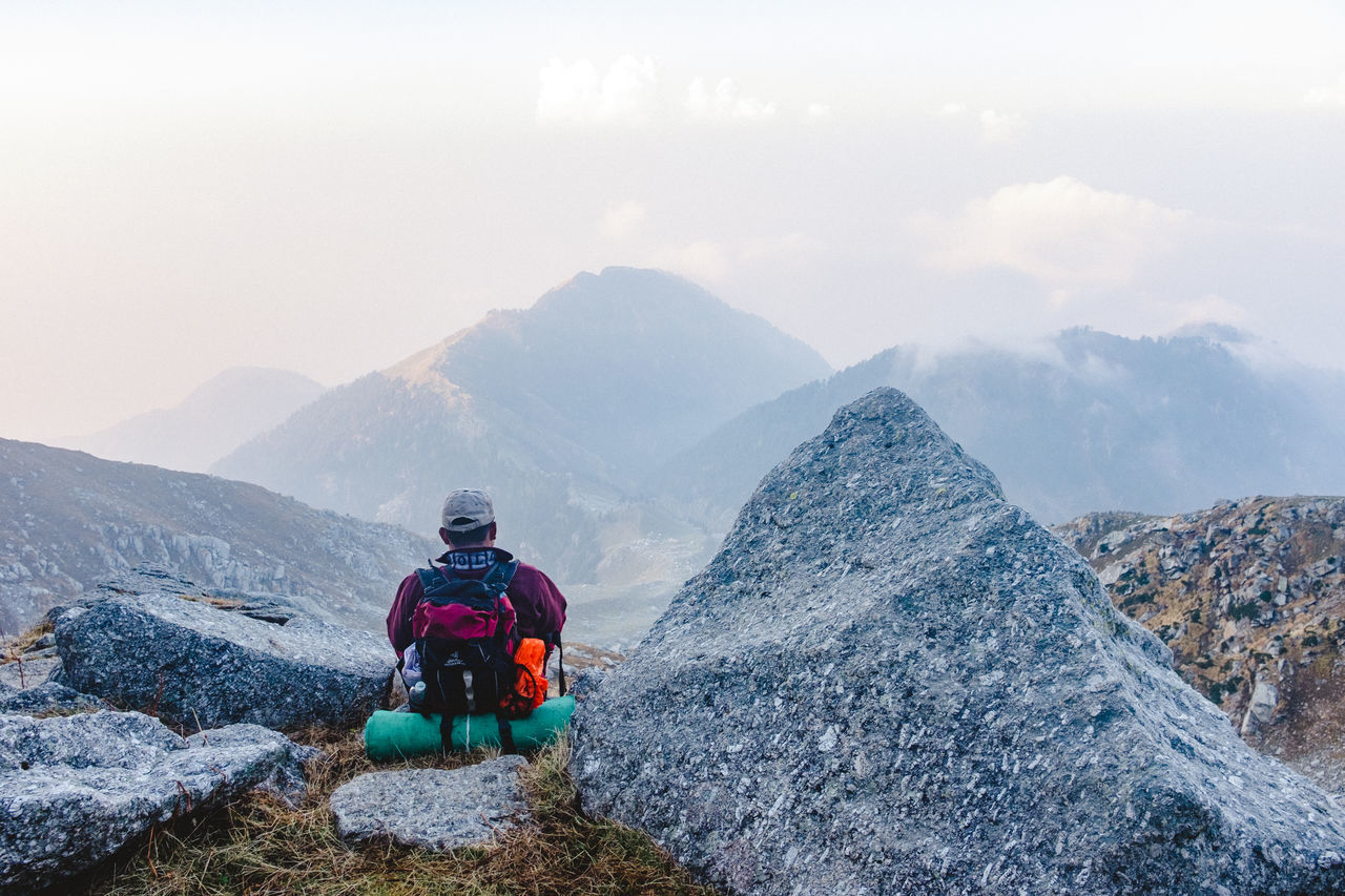 Rear View Of Hiker Sitting By Rock On Mountain Against Sky