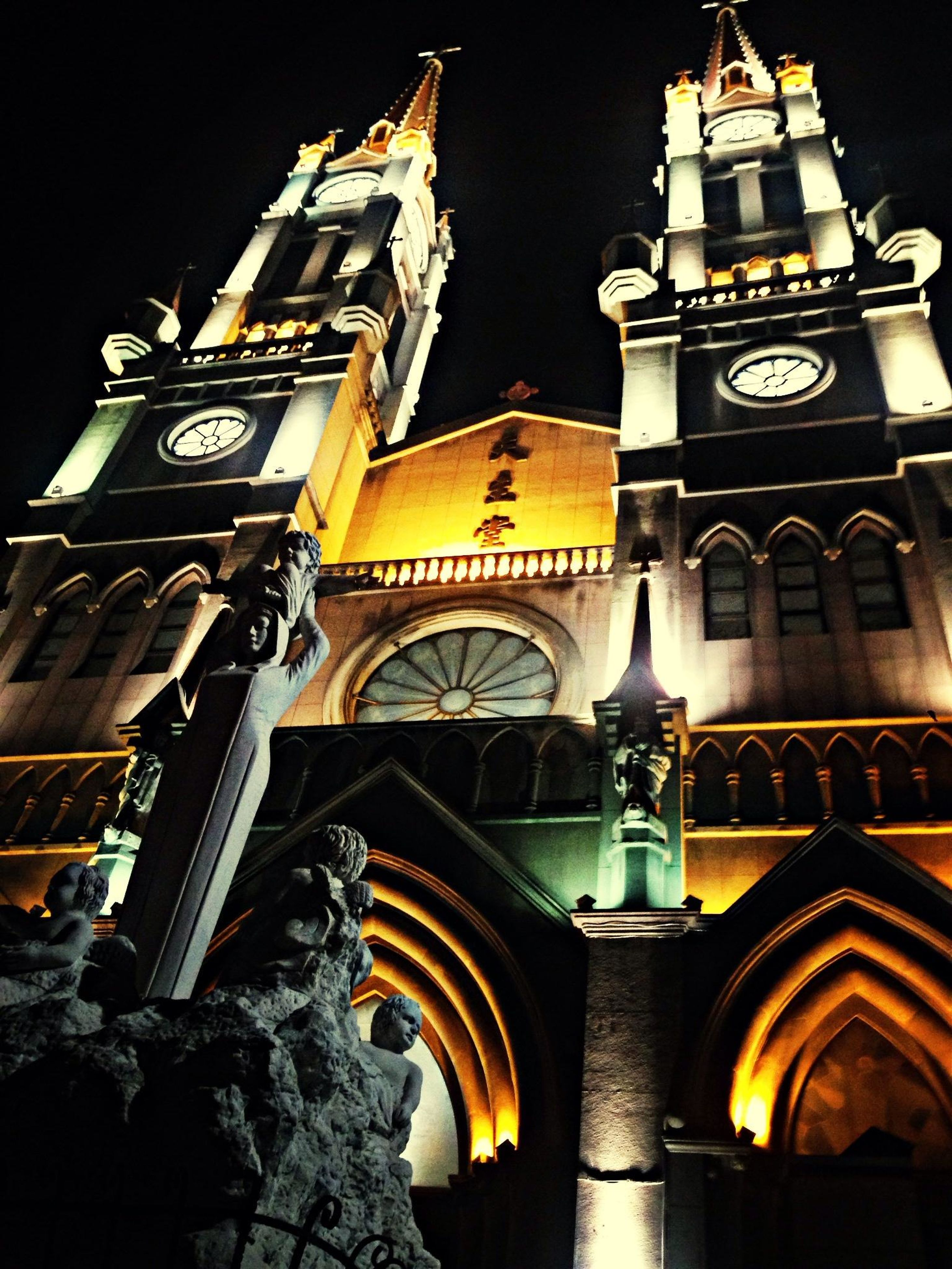 architecture, building exterior, built structure, low angle view, illuminated, night, arch, clock tower, text, place of worship, church, city, religion, building, outdoors, clear sky, history, no people, sky