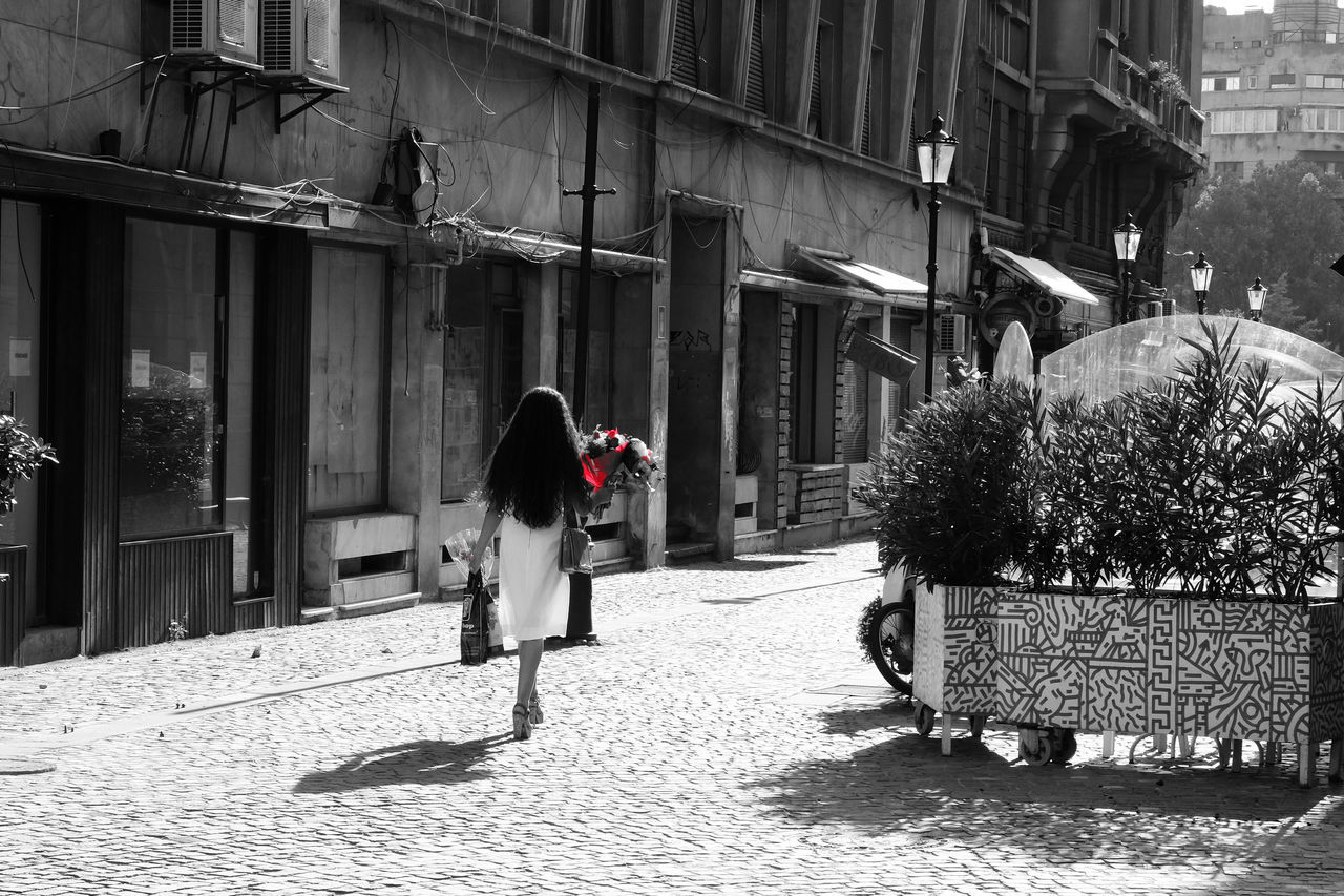 Woman in a white dress with red flowers in her hands walking downtown Bucharest Architecture Blackandwhite Bucharest Bw Photography Bw_collection City Life Day Downtown Bucharest Historical Building Old Buildings Old House Old Town Person Red Flowers Romania Street Photographer Street Photography Streetphoto_bw Streetphotographers Travel Photography Visiting Bucharest Walking White Dress Woman Womanity
