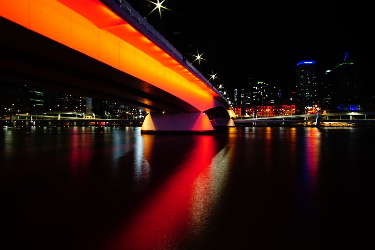 illuminated, night, bridge - man made structure, architecture, built structure, reflection, river, waterfront, city, connection, building exterior, multi colored, transportation, city life, water, outdoors, cityscape, no people, travel destinations, sky