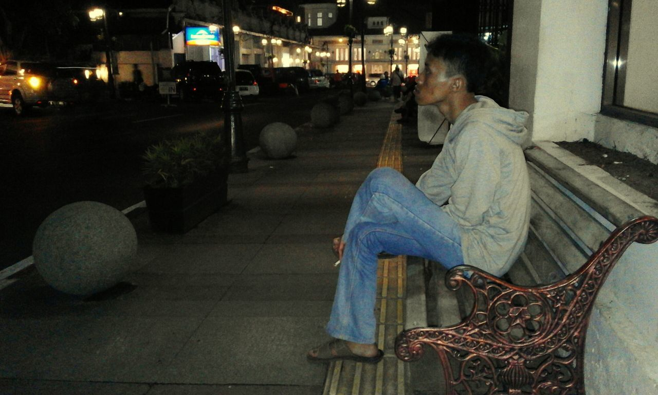 real people, night, one person, sitting, full length, lifestyles, men, architecture, women, building exterior, outdoors, people