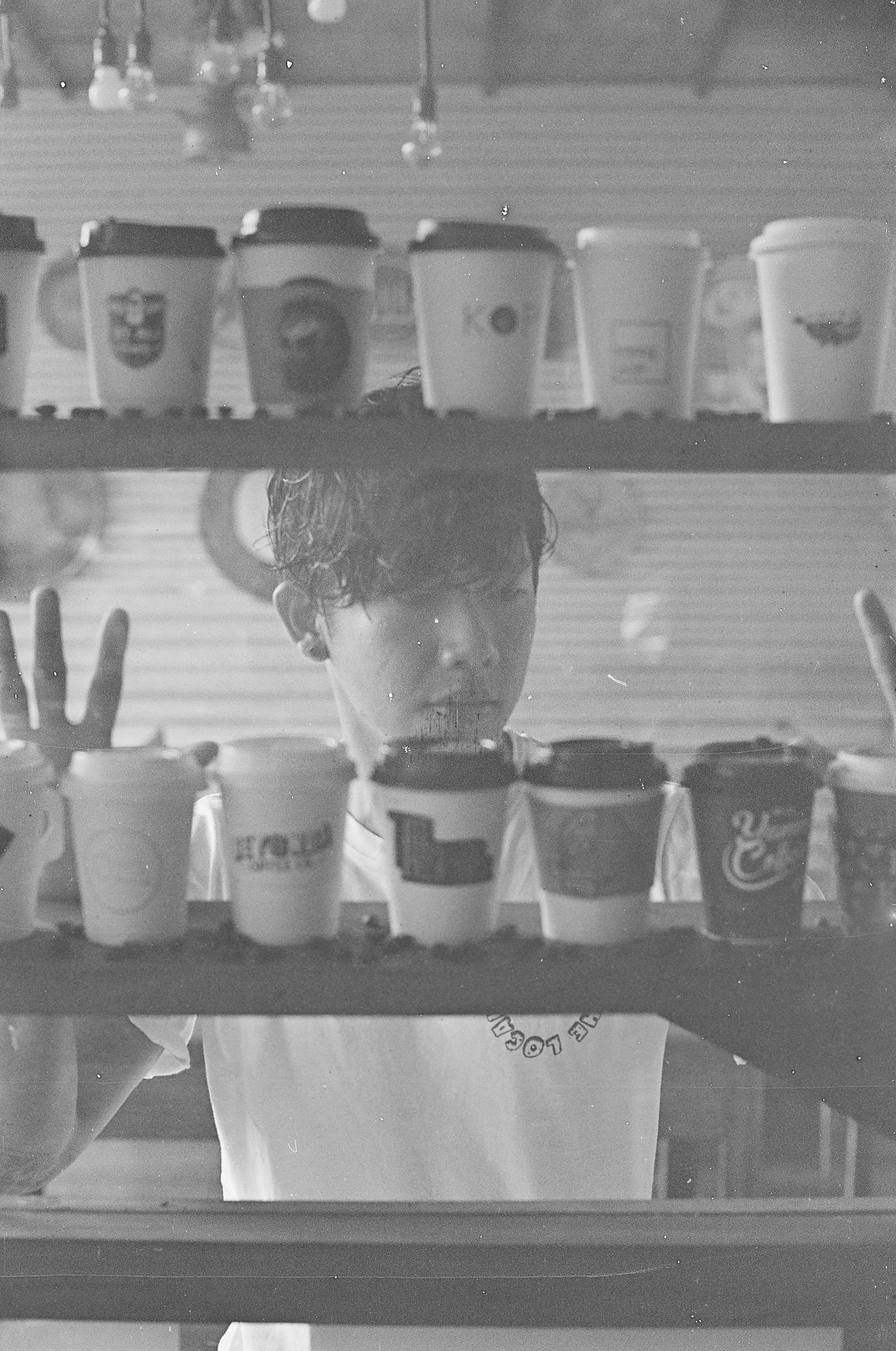 the coffee invasion is alive an well in ubud bali 35mm Film Analogue Photography Bali Bali, Indonesia Close-up Coffe Tumbler Coffee Coffee Culture Coffee Cups Copy Space Day Film Photography Filmisnotdead Ilford Indonesia_photography Indoors  Large Group Of Objects Moody Pattern Pieces Portrait Of A Man  Shelf Takeaway Cups Through A Window Variation Young Adult