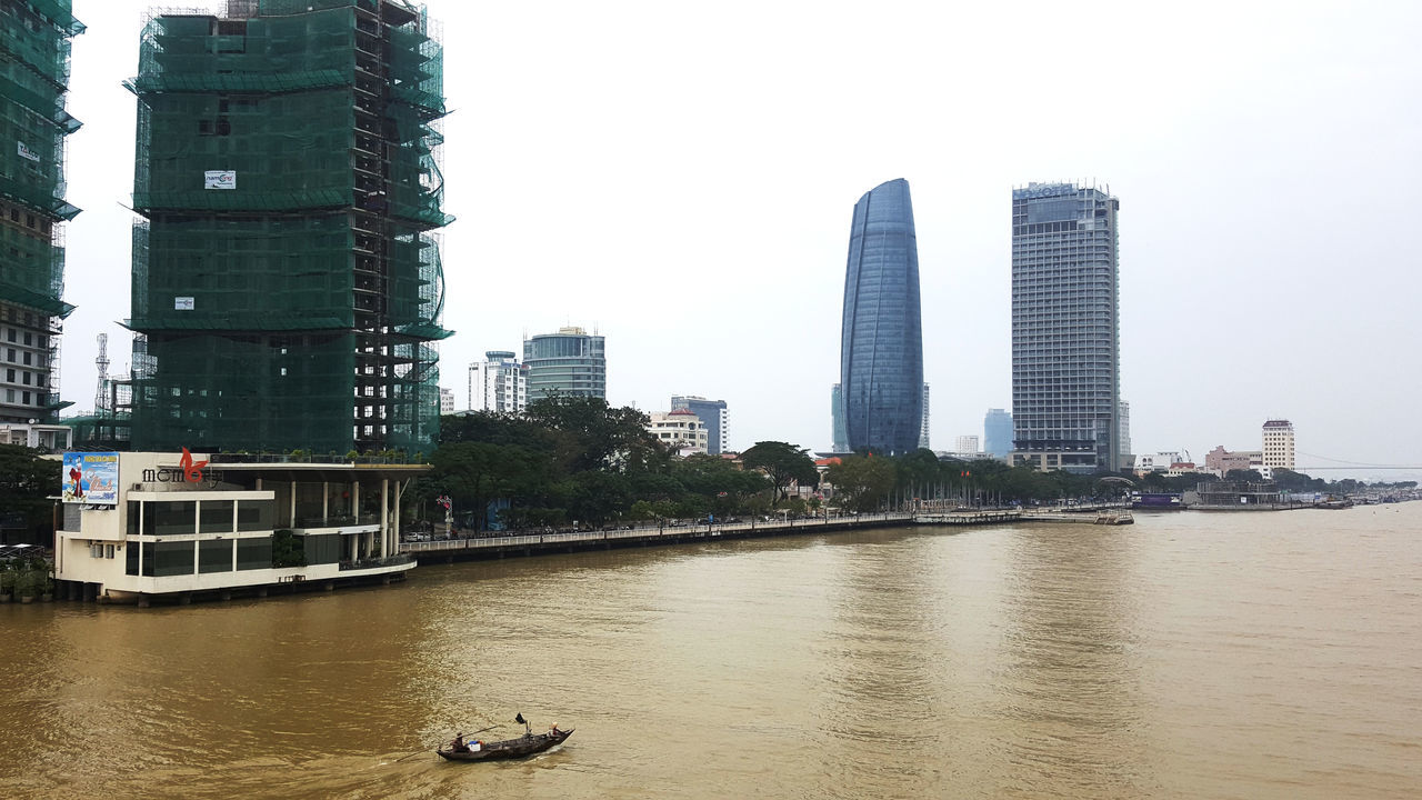 Boat on muddy Han River after days of rain in Da Nang, Vietnam. Photo shows Memory Lounge nightclub on the river outside Hilton Hotel under construction. In background is Novotel hotel. Architecture Boats City Cityscape Construction Da Nang Han River Hotels Modern Muddy Nightclubs Outdoors River Skyscraper Travel Destinations Urban Skyline Venues Vietnam Water Weather