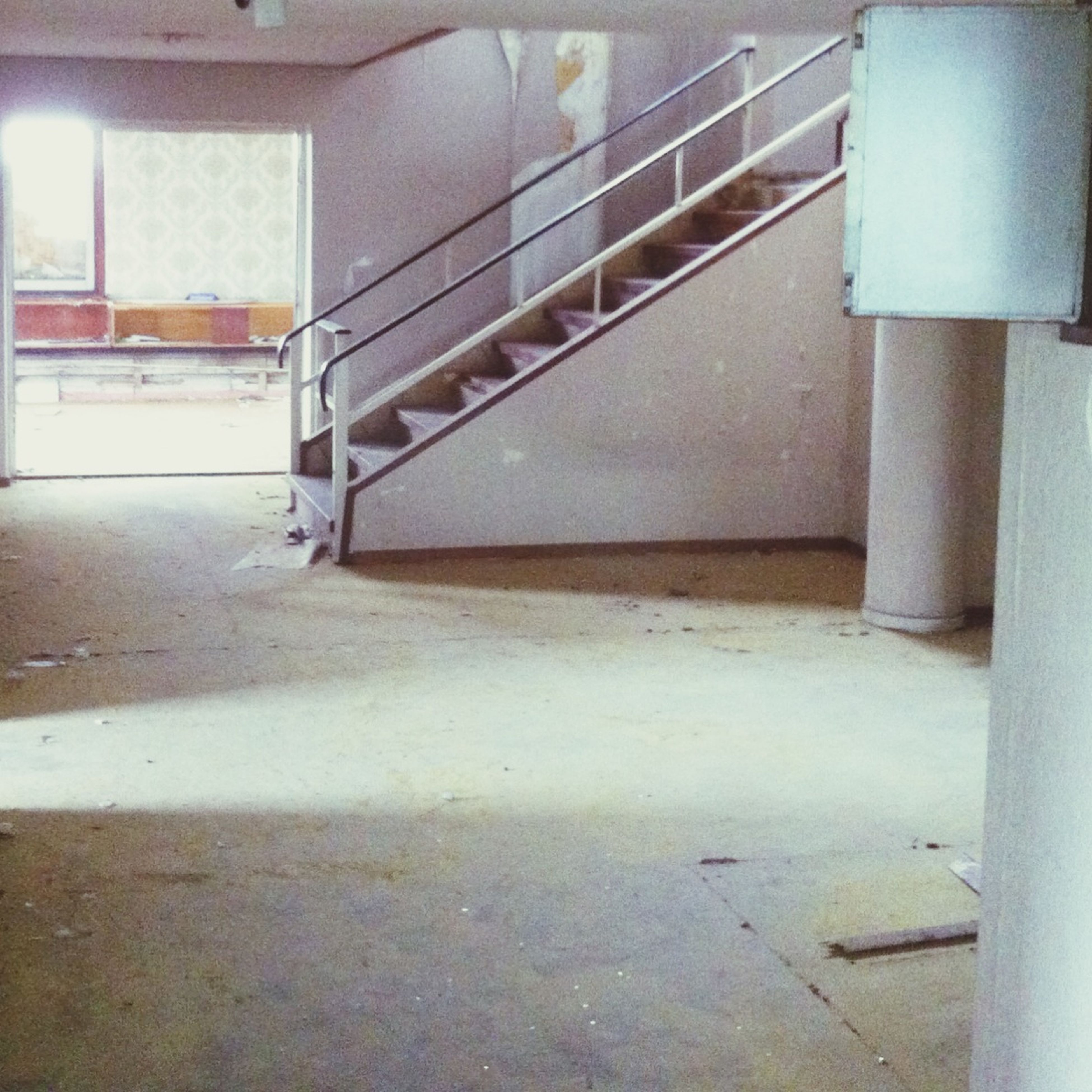 indoors, steps, architecture, built structure, steps and staircases, staircase, railing, wall - building feature, empty, the way forward, sunlight, no people, absence, metal, high angle view, day, building, transportation, wall, door