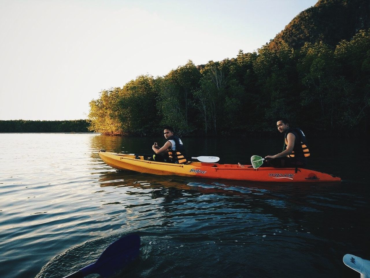 tree, leisure activity, river, nature, two people, togetherness, real people, water, oar, outdoors, day, nautical vessel, men, lifestyles, vacations, adventure, sitting, kayak, women, rowing, clear sky, sky, beauty in nature, people