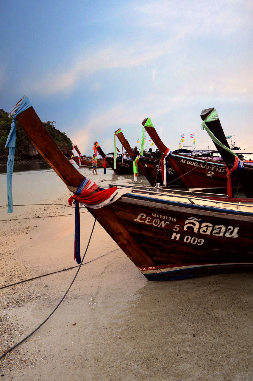 nautical vessel, transportation, beach, mode of transport, sand, moored, sky, outdoors, day, nature, wood - material, no people, longtail boat, sea, water, close-up