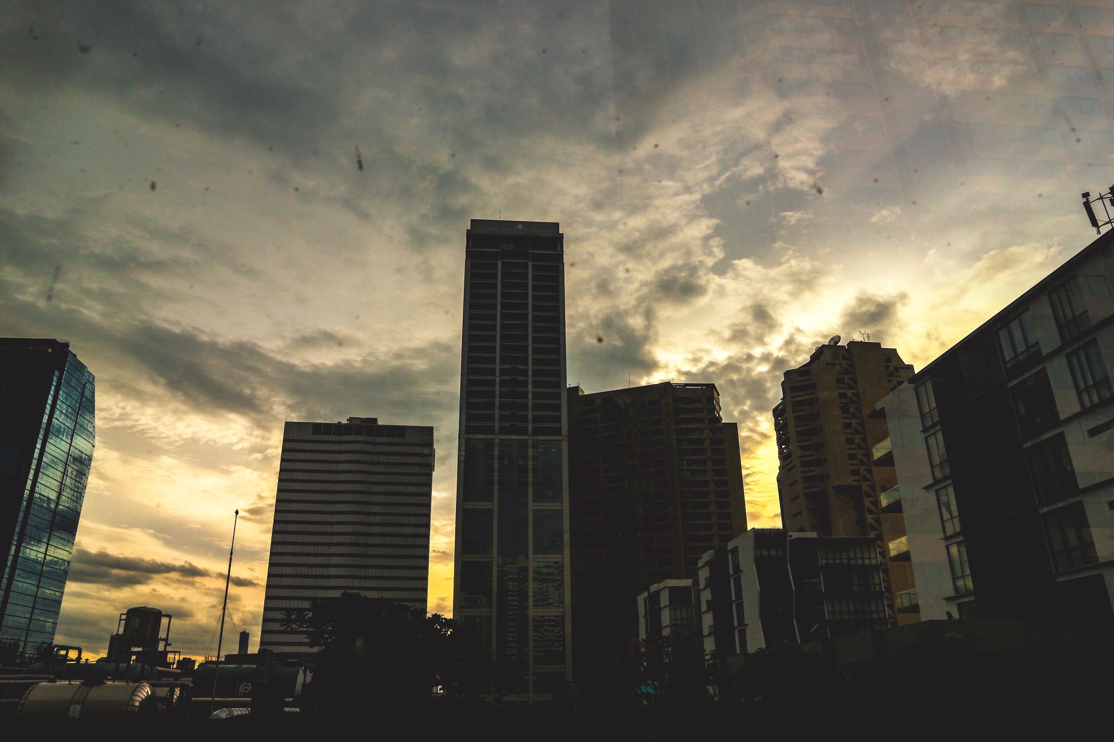 building exterior, architecture, built structure, city, skyscraper, sky, office building, cloud - sky, modern, low angle view, tall - high, sunset, tower, building, urban skyline, cloudy, city life, cloud, cityscape, outdoors, development, skyline, no people, tall, capital cities, weather, overcast, nature