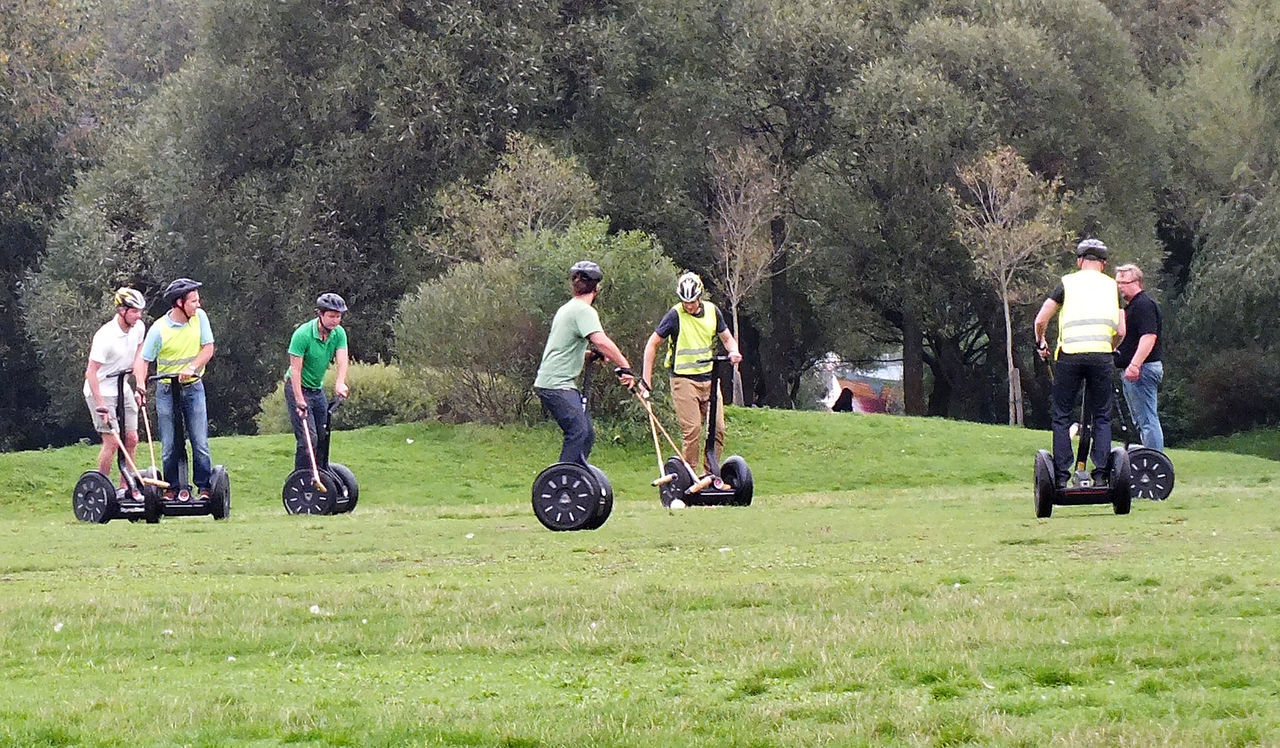 A group of youths playing Segway Crocket in Stockholm, Sweden Stockholm, Sweden Adult Day Field Full Length Crocket Golfer Grass Green - Golf Course Green Color Landscape Leisure Activity Lifestyles Men Nature Outdoors People Real People Segway Fun Segway Polo Segways In Stockholm Sport Togetherness Transportation