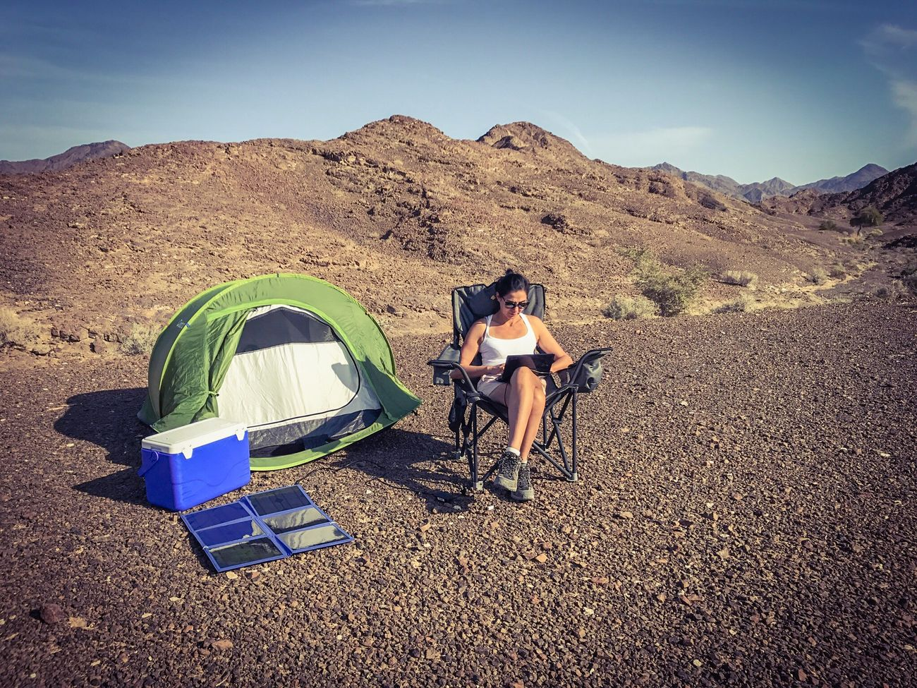 Woman using her laptop in a remote area, here the desert of rocks of the mountains of Ras Al Khaimah, and charging it with foldable solar panels. United Arab Emirates Real People Sunlight Sitting Outdoors Sky Nature Leisure Activity Young Adult Sand Vacations Day Young Women IPhone Travel Destinations Safari Isolated United Arab Emirates Desert Green Renewable Energy Energy Solar System Foldable Campsite Camping