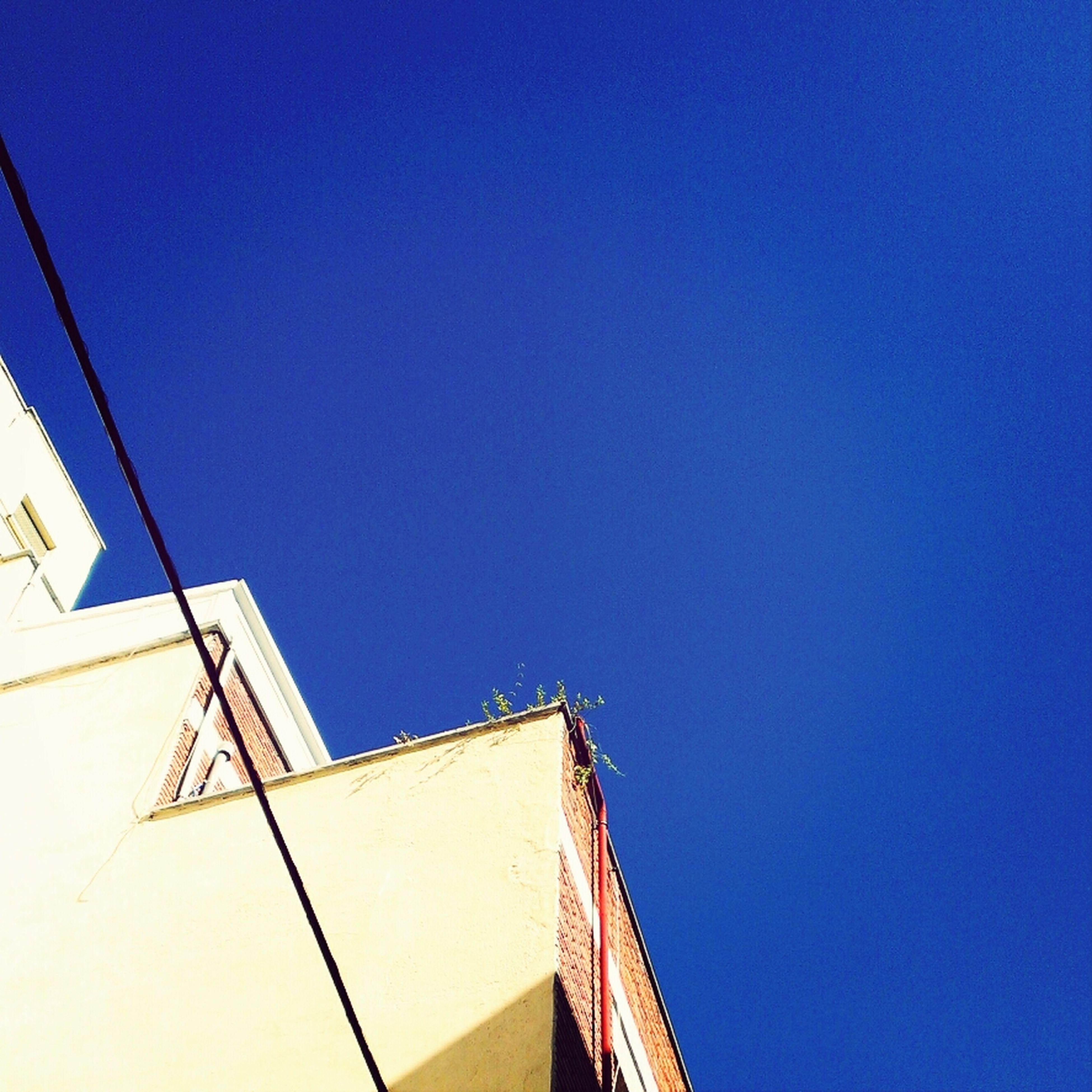 clear sky, architecture, built structure, low angle view, copy space, blue, building exterior, high section, building, outdoors, day, no people, part of, residential structure, roof, sunlight, city, house, wall - building feature, cropped