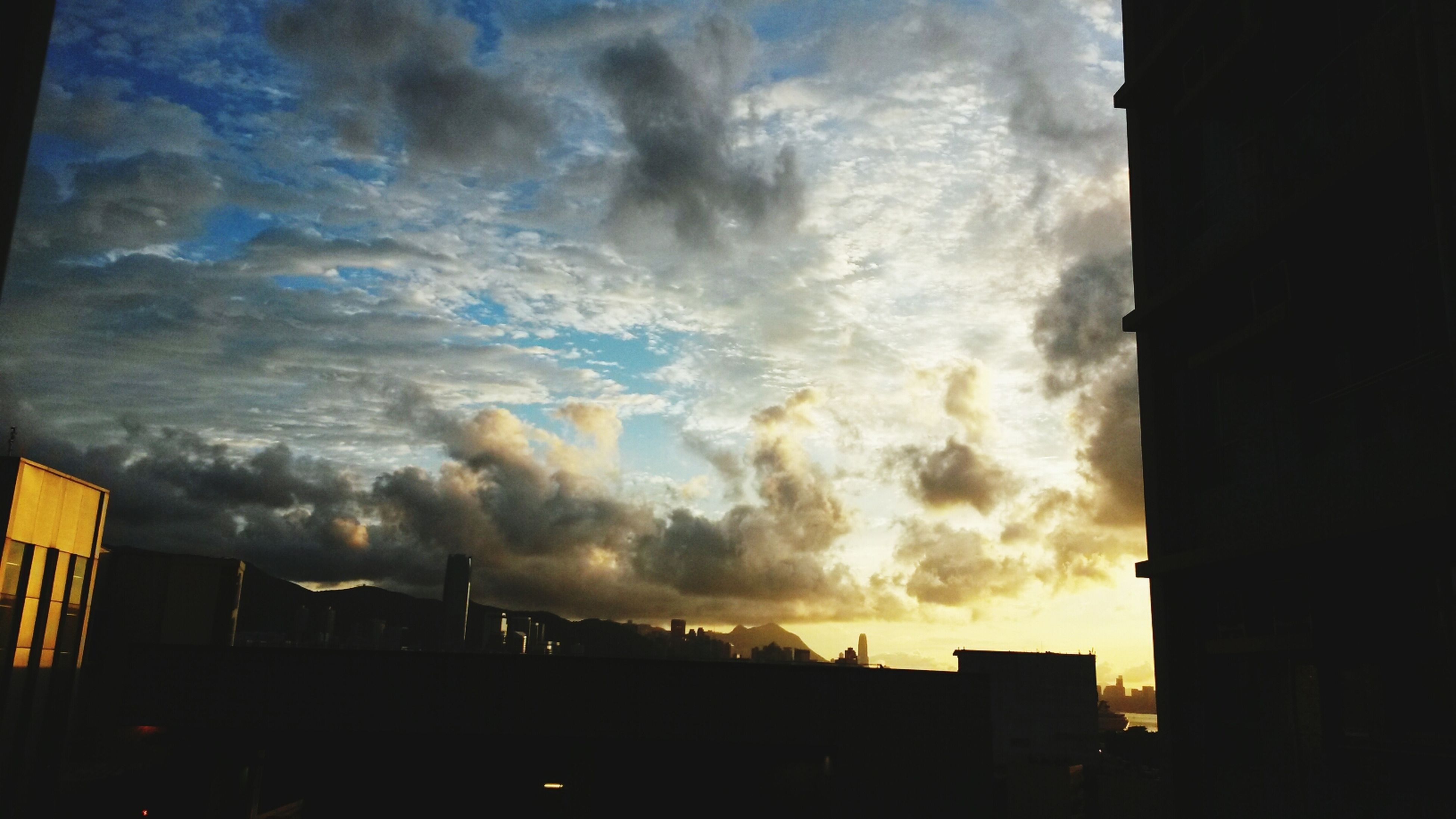 building exterior, architecture, sky, built structure, cloud - sky, cloudy, sunset, silhouette, weather, storm cloud, low angle view, city, cloud, building, overcast, dramatic sky, dusk, residential building, atmospheric mood, residential structure