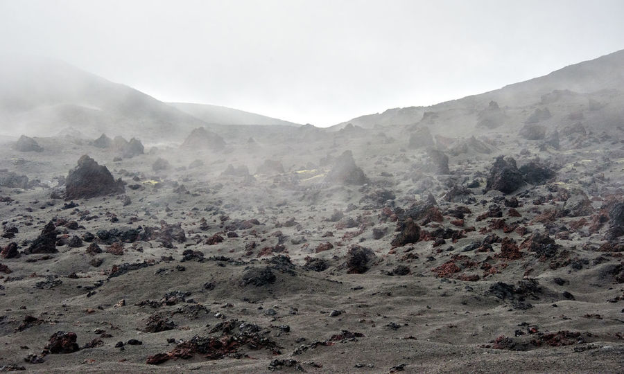 Volcanic desert with standing rocks at Kamchatka Adventure Beauty In Nature Day Far East Fog Kamchatka Landscape Mountain Mountain Range Natural Disaster Nature No People Outdoors Russia Scenics Sky Snow Travel Destinations