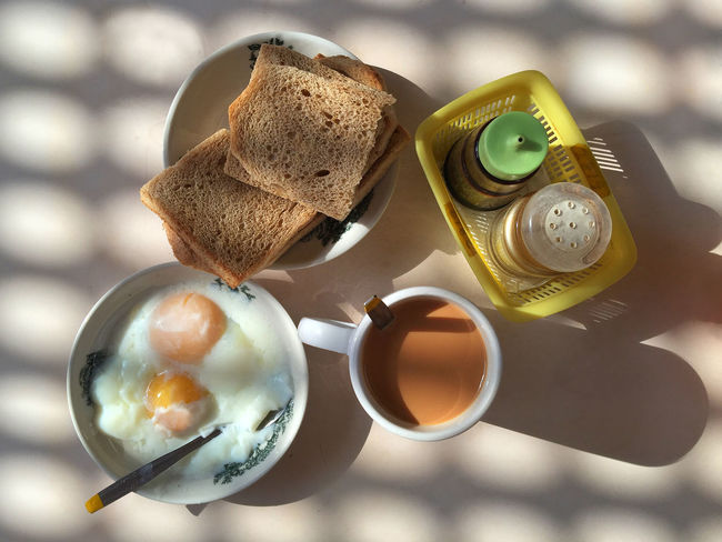 i enjoy my favorite local breakfast set ~ toast, half boiled eggs with black sauce and pepper, and milk tea under the warm morning sunlight. :) ASIA Breakfast Culture Eggs Hawker Centre Hawker Food Lifestyle Light And Shadow Milk Tea Morning My Favorite Breakfast Moment Outdoors Shade Shadow Sunlight Toast View From Above Fine Art Photography A Bird's Eye View