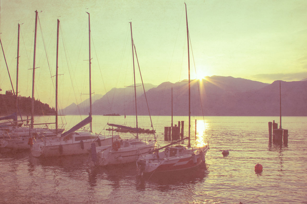 Boats Moored In Lake By Mountain During Sunset