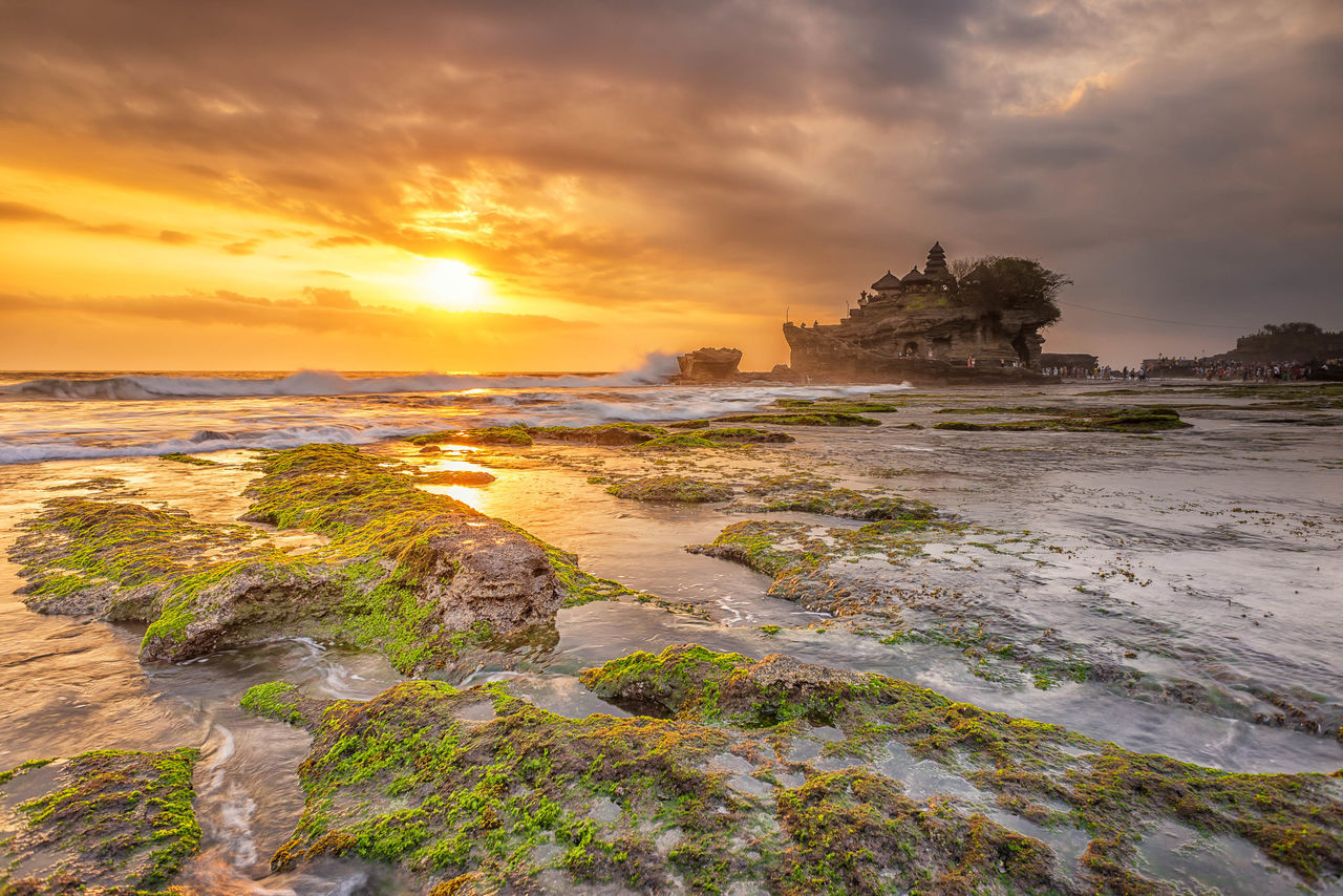 Sunset at Tanah Lot, a popular tourist attraction in Bali, Indonesia. Architecture Bali Beach Cliff Clouds Clouds And Sky Cloudscape Horizon Over Water INDONESIA Island Moss Nature Outdoors Pura Reflection Rock Formation Sea Sunset Sunsets Tanah Lot Temple Tourist Tourist Attraction  Travel Destinations Waves
