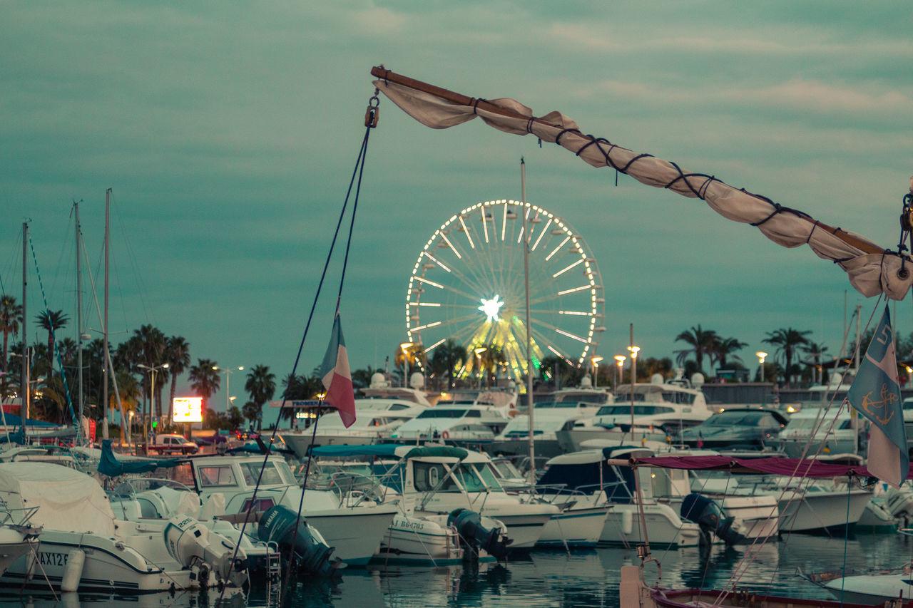 ferris wheel, amusement park, arts culture and entertainment, sky, amusement park ride, outdoors, big wheel, built structure, nautical vessel, day, water, no people, nature