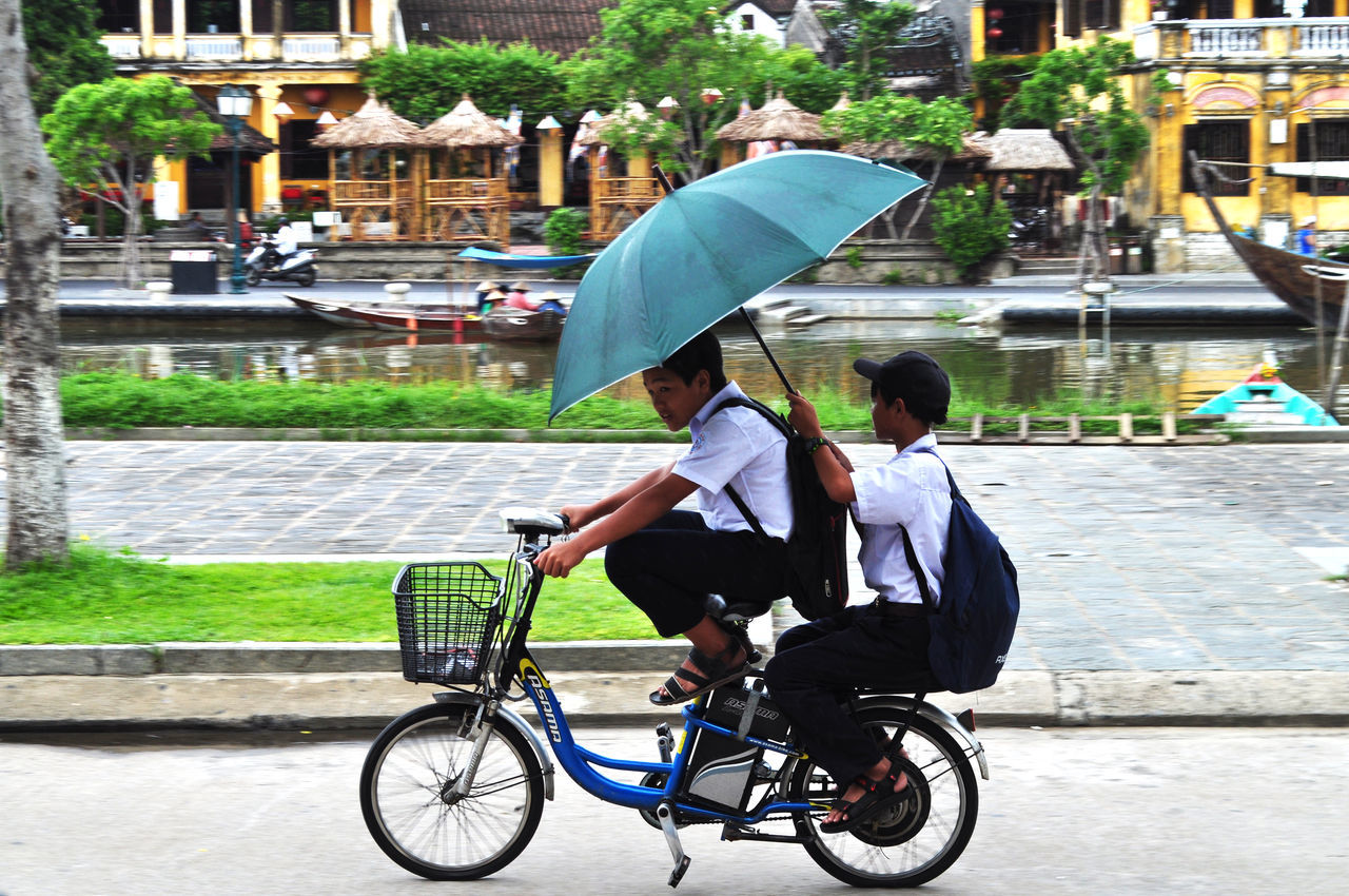 Schoolboys on electric bike in Hoi An, Vietnam. Architecture Backpacks Cycling Editorial  Electric Bikes Friends Hoi An Lifestyles Outdoors Rivers Sandals Schoolboys Street Transportation Trees Umbrellas Vietnam Water Weather