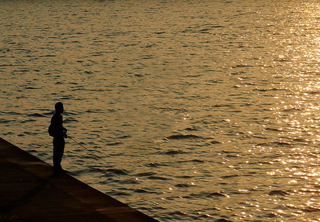 a man fishing near the river Beauty In Nature Day Fishing Full Length Horizon Over Water Nature One Person Outdoors People Real People Rippled Scenics Sea Standing Sunset Tranquil Scene Tranquility Water