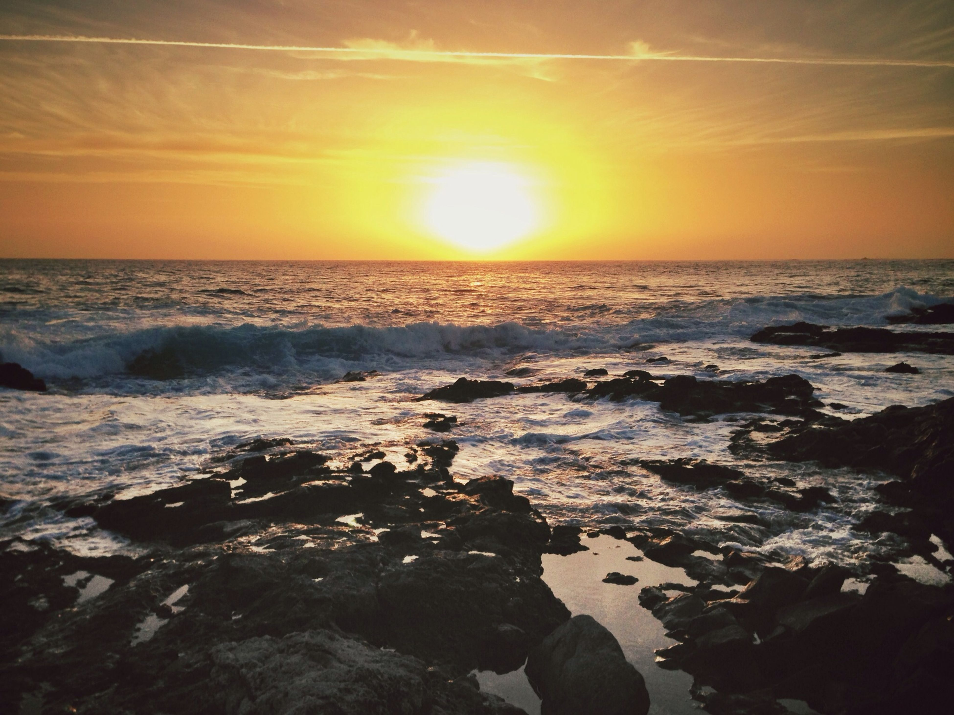 sunset, sea, water, horizon over water, scenics, beauty in nature, sun, beach, tranquil scene, orange color, tranquility, shore, sky, nature, rock - object, idyllic, wave, sunlight, reflection, remote