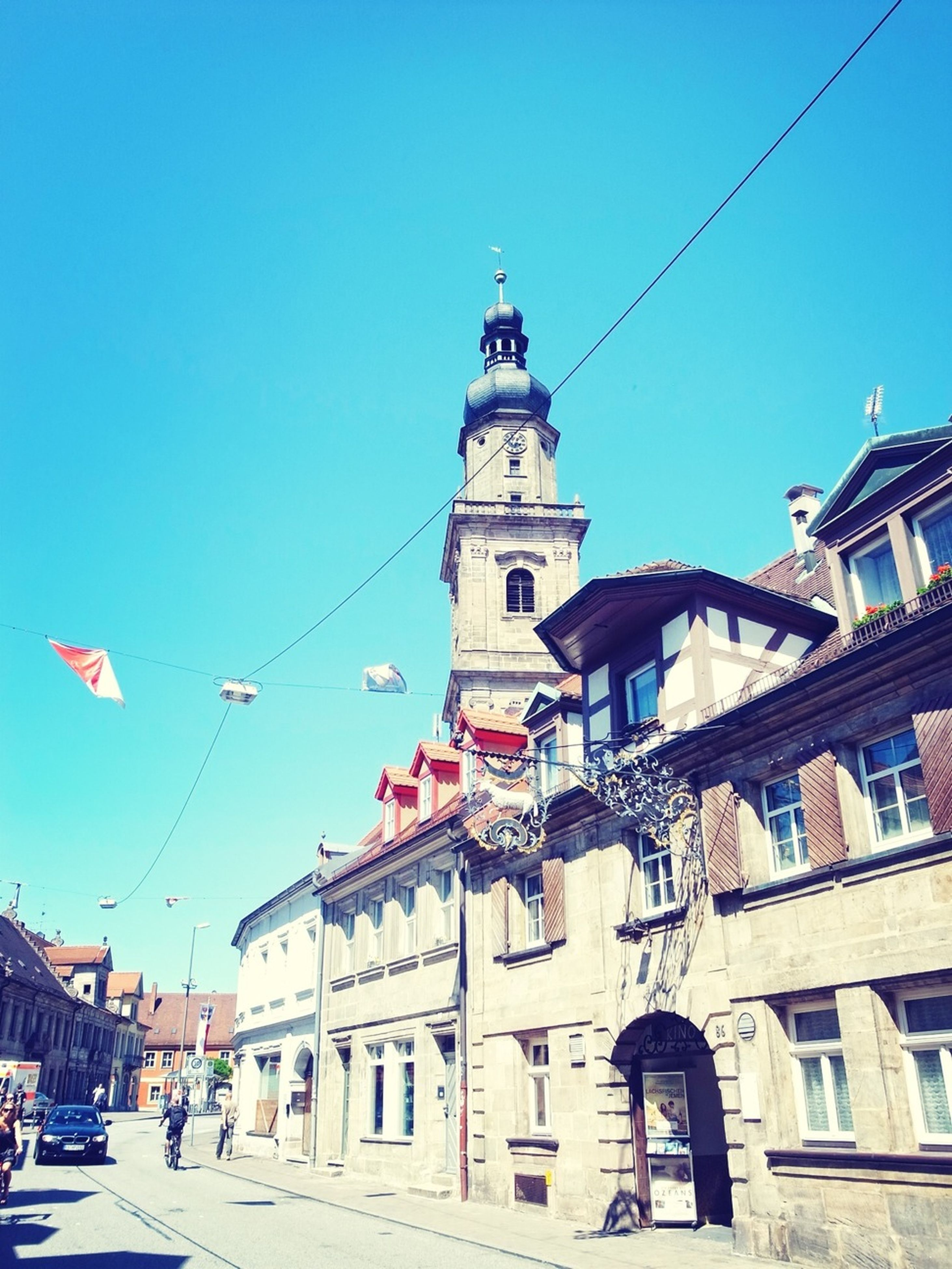 building exterior, architecture, built structure, clear sky, blue, low angle view, city, street, street light, residential building, day, sunlight, building, residential structure, religion, church, outdoors, window, old town, facade