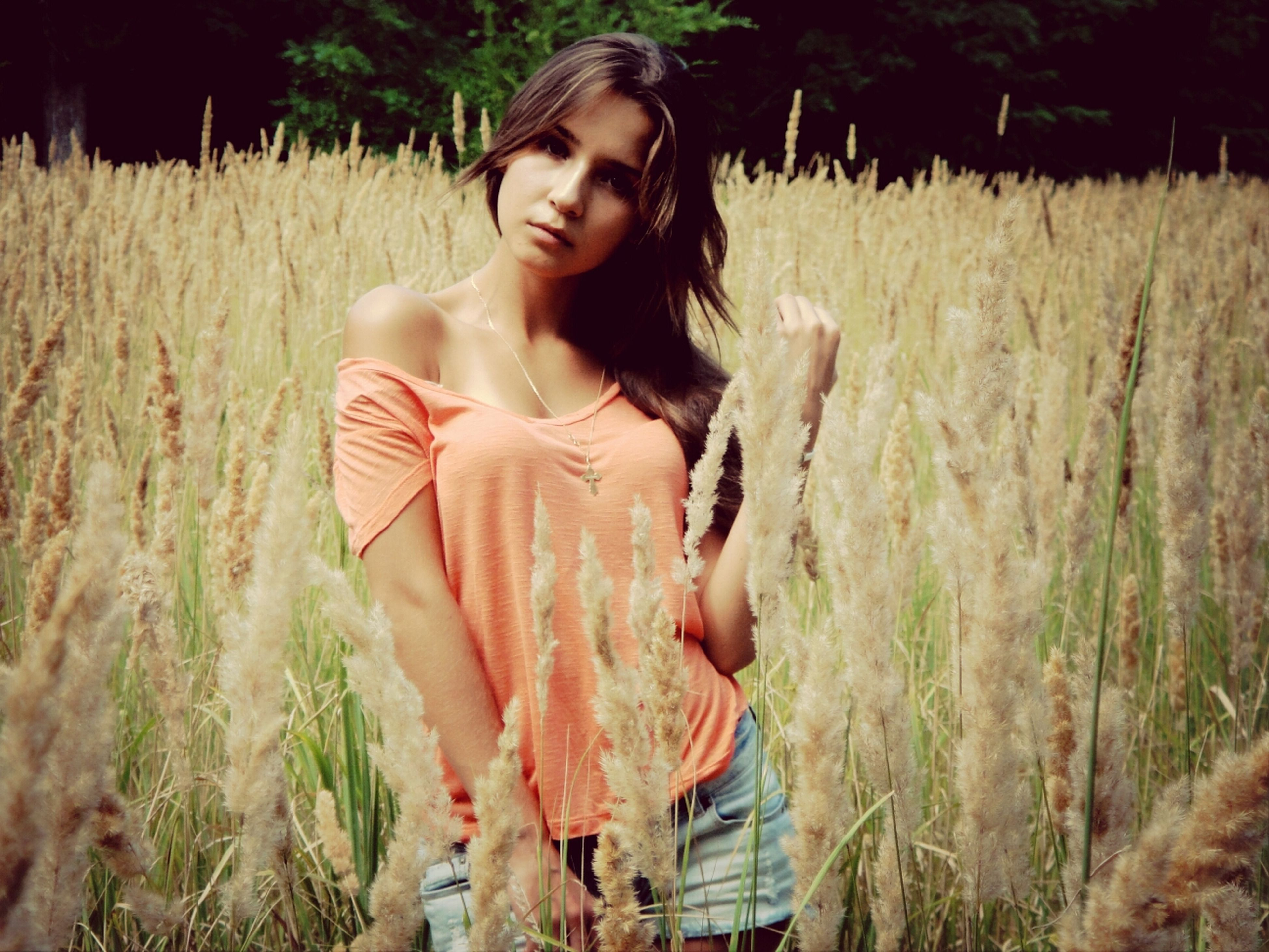 young adult, person, young women, lifestyles, casual clothing, leisure activity, three quarter length, front view, holding, long hair, field, waist up, standing, grass, portrait, looking at camera, full length