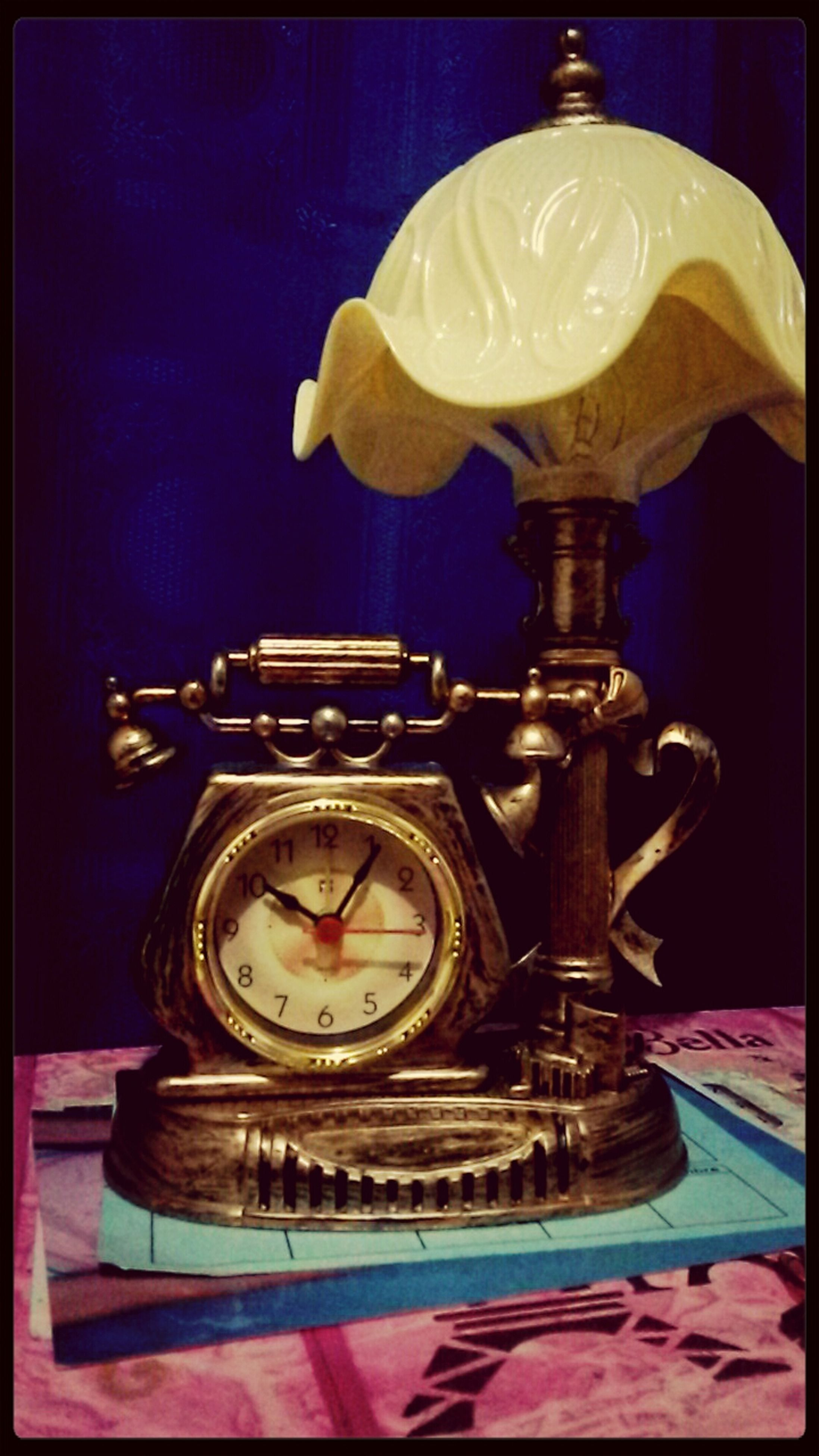 indoors, close-up, ornate, antique, clock, transfer print, still life, old-fashioned, gold colored, table, single object, illuminated, time, auto post production filter, glass - material, luxury, no people, retro styled, lighting equipment, studio shot
