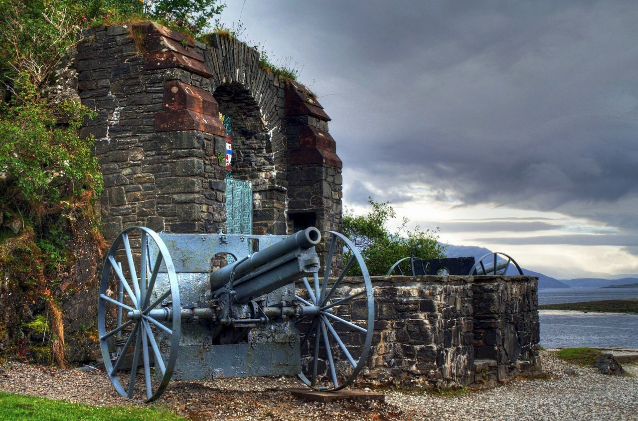 history, weapon, cannon, cloud - sky, sky, built structure, day, architecture, canon, no people, field, nature, outdoors, building exterior, water, beauty in nature, tree, military