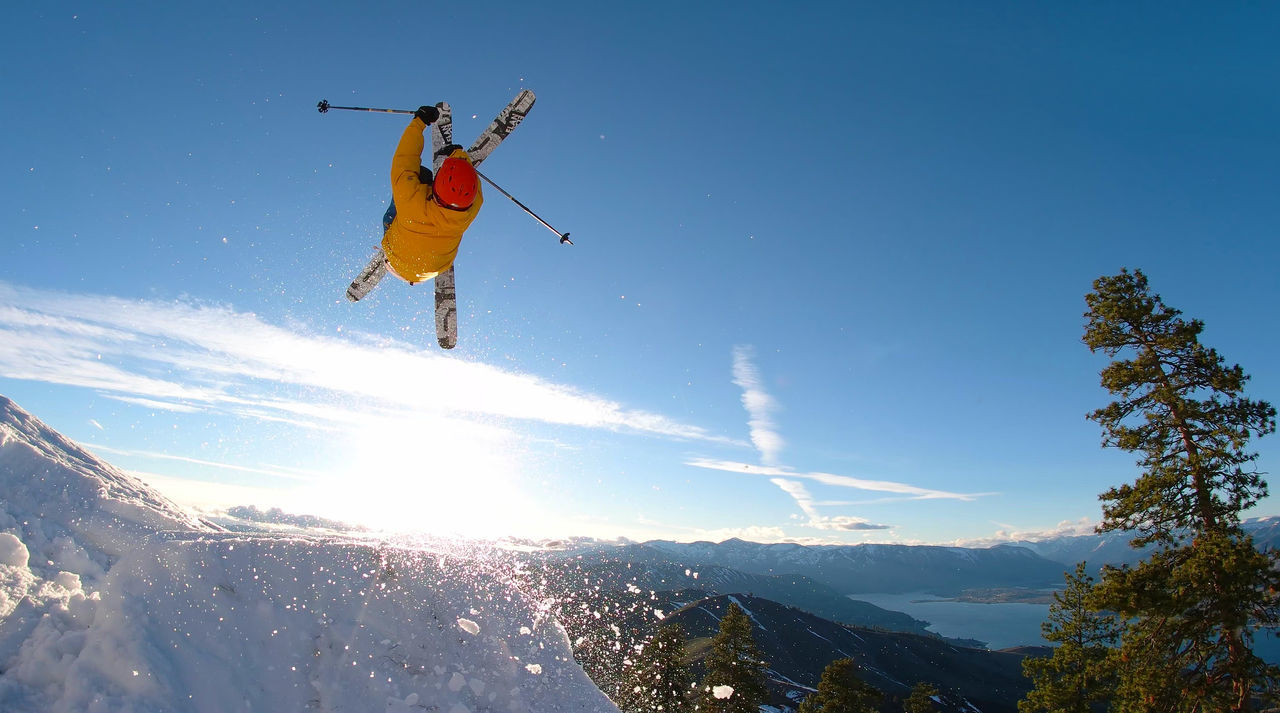 Person Jumping While Skiing On Snowcapped Mountain Against Sky